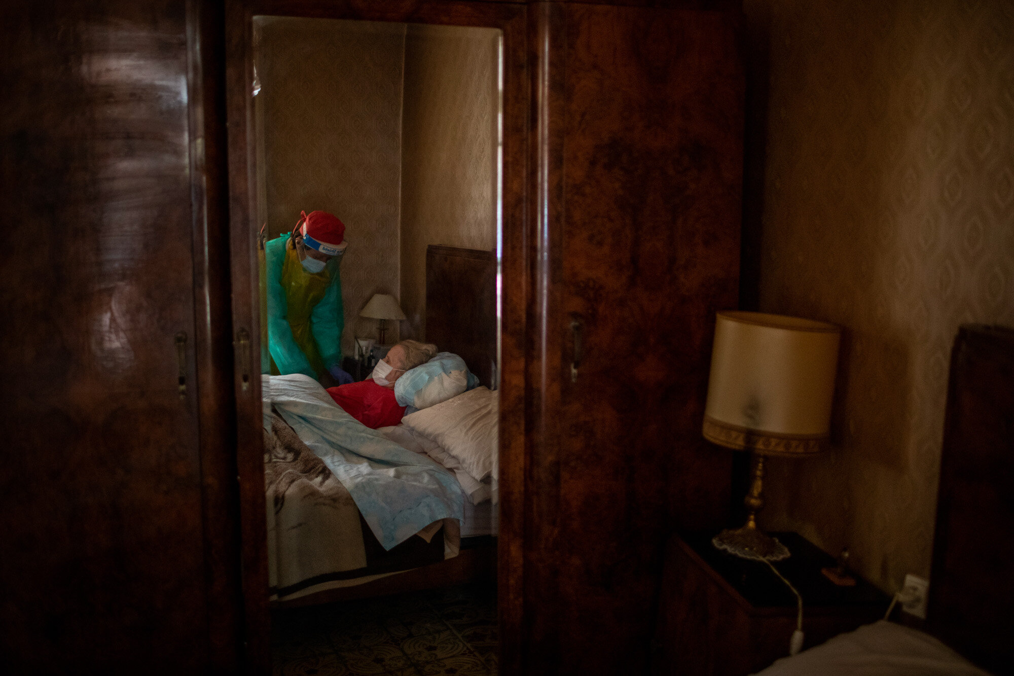 """Josefa Ribas, 86, who is bedridden and suffers from dementia, is attended to by nurse Laura Valdes during a home care visit in Barcelona, Spain, on April 7, 2020. Ribas' husband, Jose Marcos, fears what will happen if the coronavirus enters their home and infects them. """"I survived the post-war period (of mass hunger). I hope I survive this pandemic,"""" he said. (AP Photo/Emilio Morenatti)"""