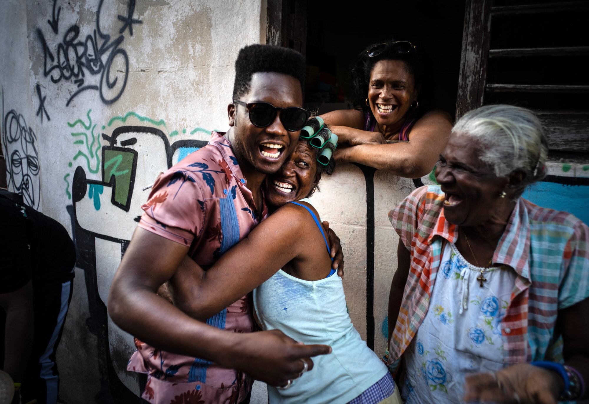 Cuban singer Cimafunk hugs a woman during a music conga through the streets of Cuba's Old Havana neighborhood during the 35th Havana International Jazz Festival on Jan. 15, 2020. (AP Photo/Ramon Espinosa)