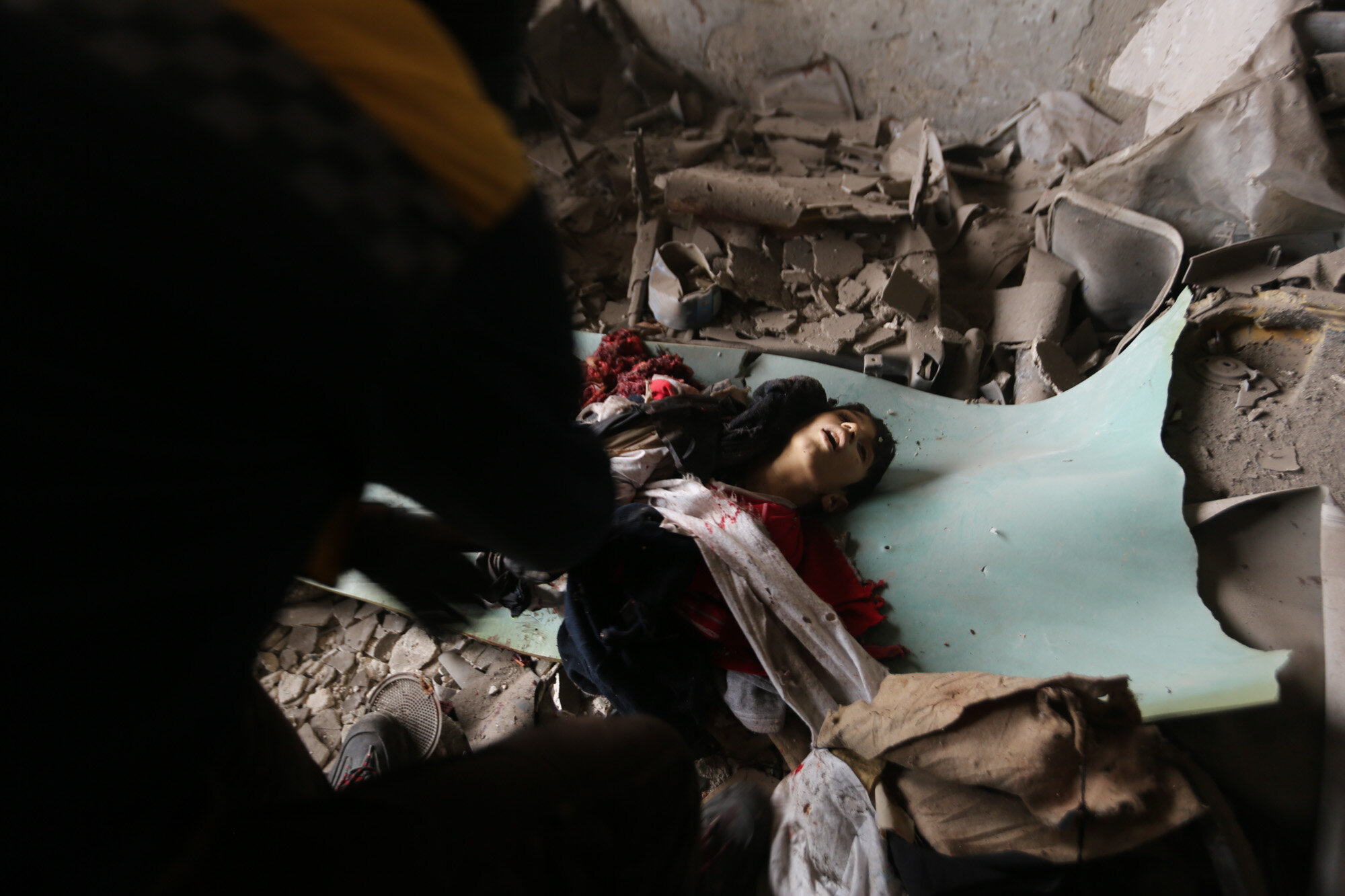 An emergency crew recovers the body of a boy killed in a government airstrike in the city of Idlib, Syria on Feb. 11, 2020. (AP Photo/Ghaith Alsayed)
