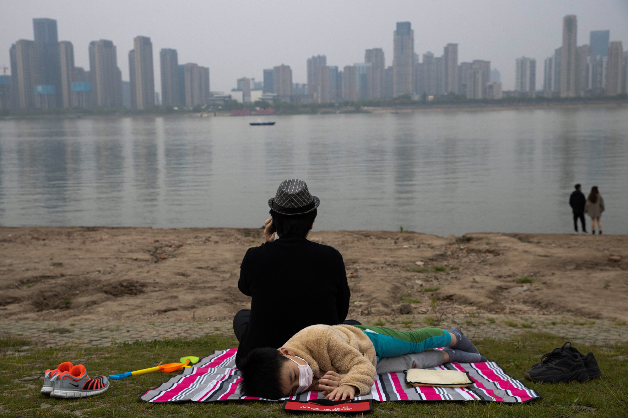 A child wearing a mask to protect against the coronavirus rests on the bank of the Yangtze River in Wuhan in central China's Hubei province on April 16, 2020. (AP Photo/Ng Han Guan)