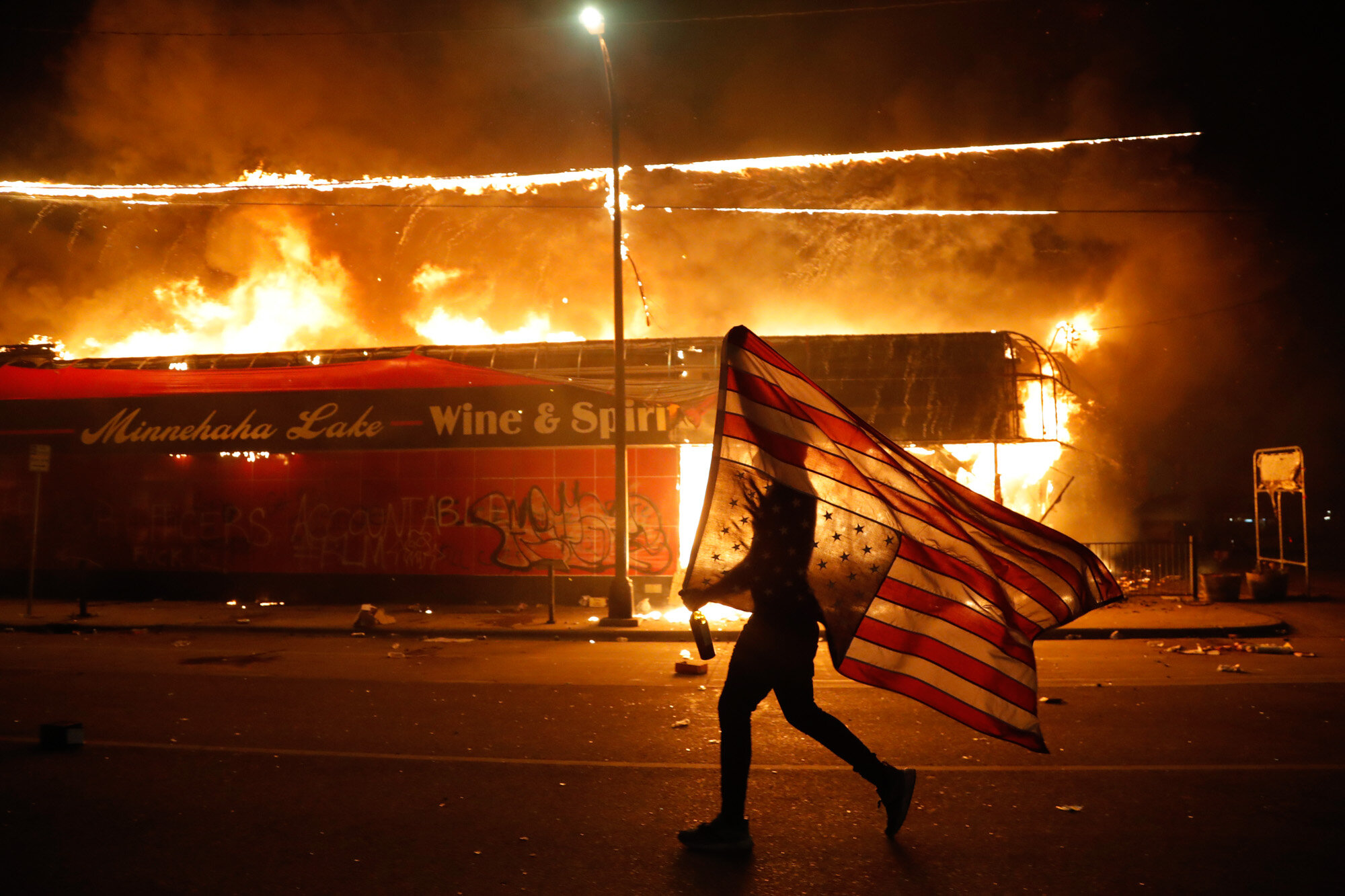 A protester carries a U.S. flag upside down as he walks past a burning building in Minneapolis on May 28, 2020, during a protest over the death of George Floyd, a Black man who died after a white Minneapolis police officer pressed a knee into his neck for several minutes. (AP Photo/Julio Cortez)