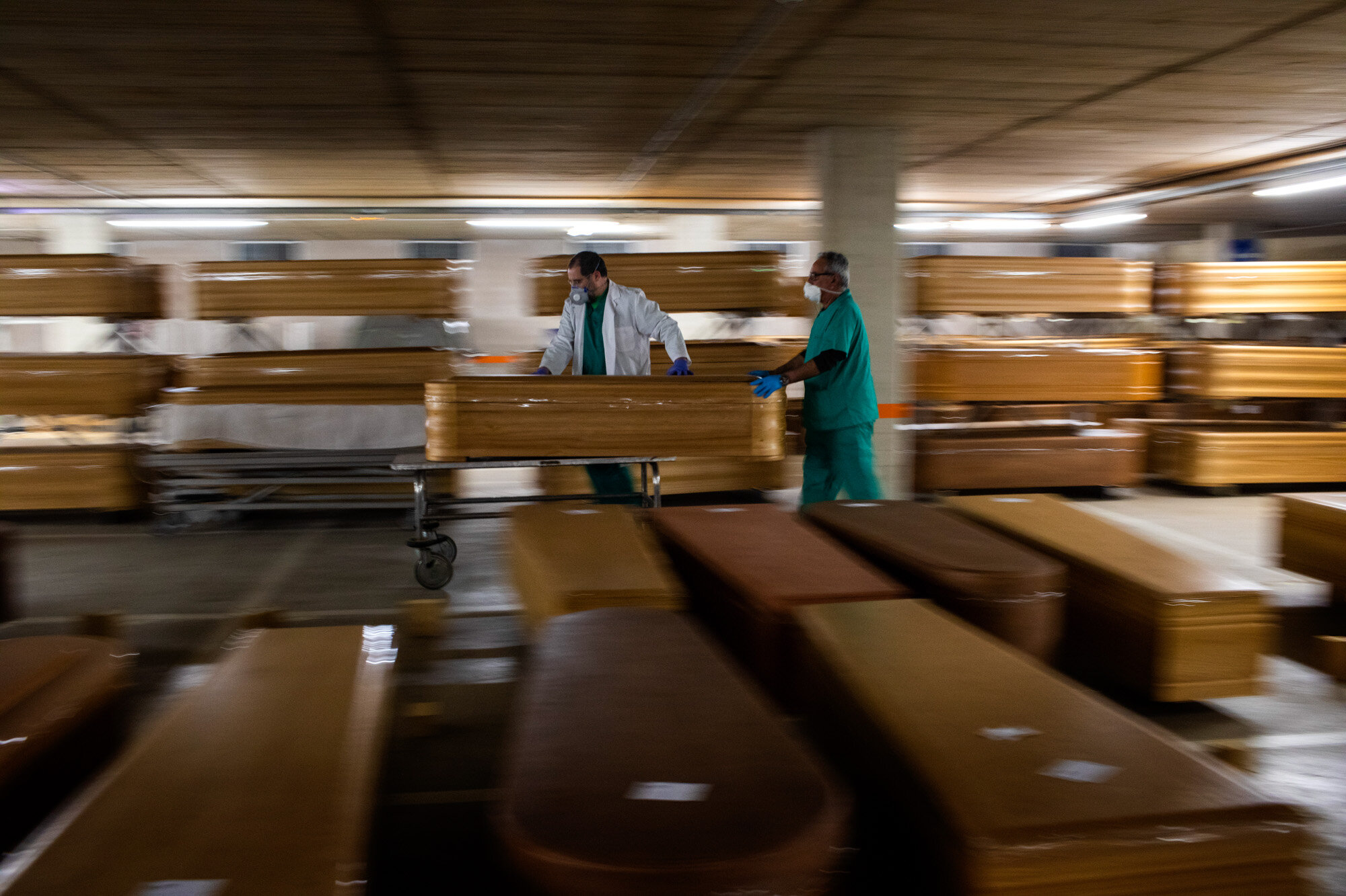 Workers move a coffin with the body of a victim of COVID-19 as other coffins are stored waiting for burial or cremation at the Collserola morgue in Barcelona, Spain, on April 2, 2020. (AP Photo/Emilio Morenatti)