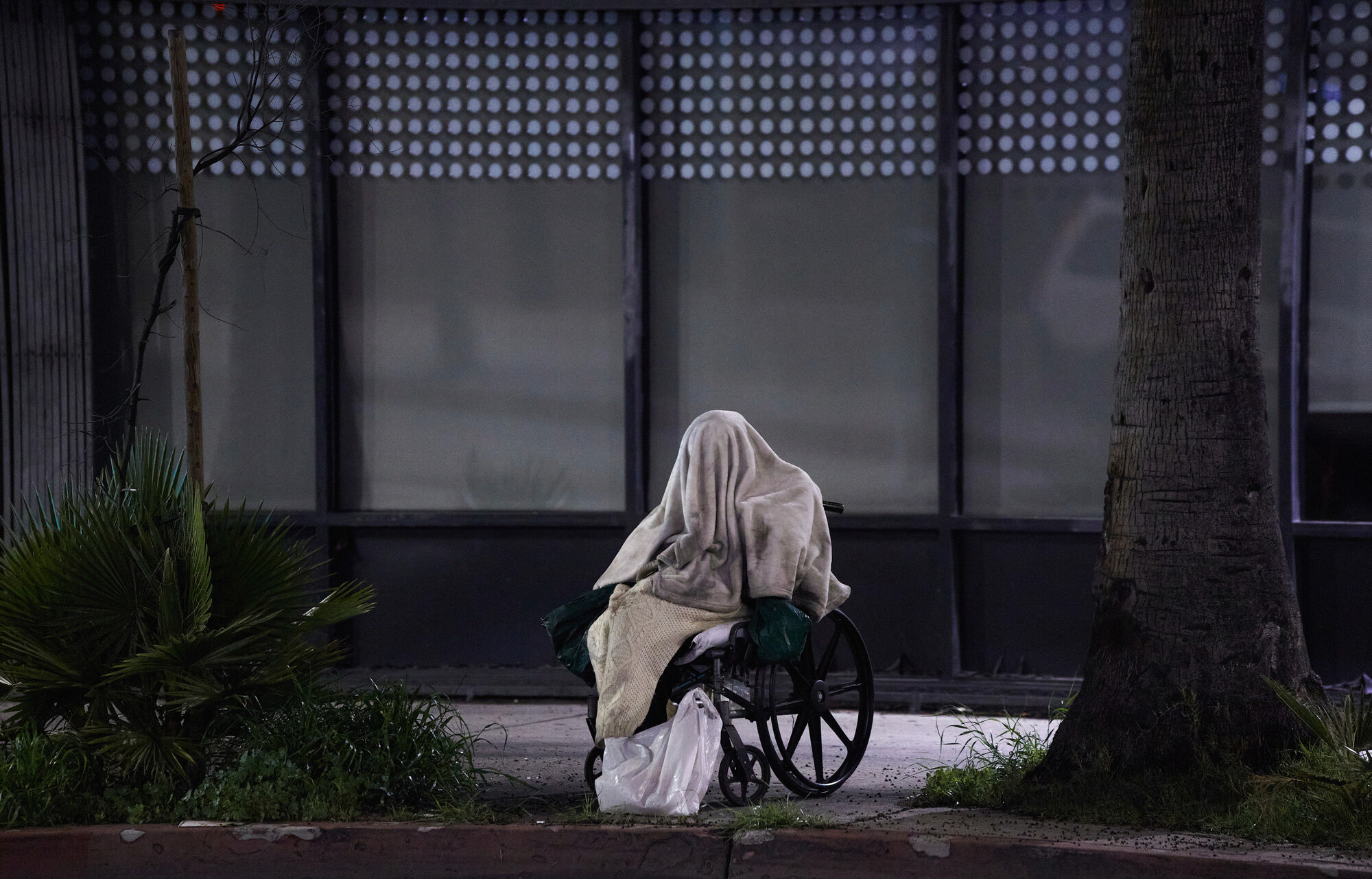 A homeless person sits in a wheelchair during rainy weather on Sunset Blvd. in the Echo Park neighborhood of Los Angeles on April 6, 2020. California Gov. Gavin Newsom signed an emergency order in mid-March to spend $150 million to help the homeless during the pandemic. (AP Photo/Damian Dovarganes)
