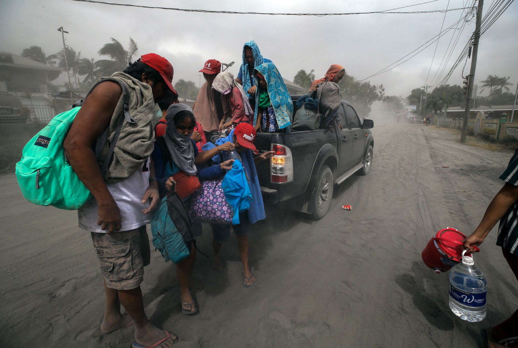 A family evacuates to safer ground as the Taal Volcano spews ash in Lemery, Batangas, southern Philippines on Jan. 13, 2020. (AP Photo/Aaron Favila)