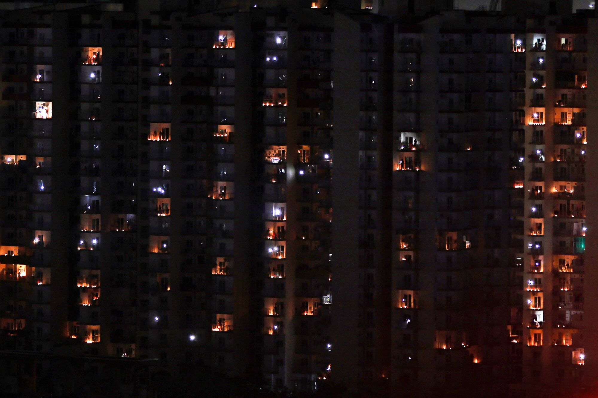 Balconies are illuminated with candles and torches to mark the country's fight against the coronavirus in Greater Noida, a suburb of New Delhi, India, on Sunday, April 5, 2020. (AP Photo/Altaf Qadri)