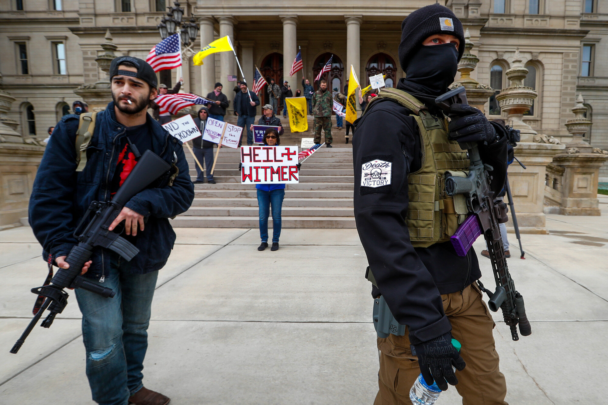 Men carry rifles near the steps of the State Capitol building in Lansing, Mich., on April 15, 2020, during a protest over Michigan Gov. Gretchen Whitmer's orders to keep people at home and businesses locked during the coronavirus outbreak. (AP Photo/Paul Sancya)