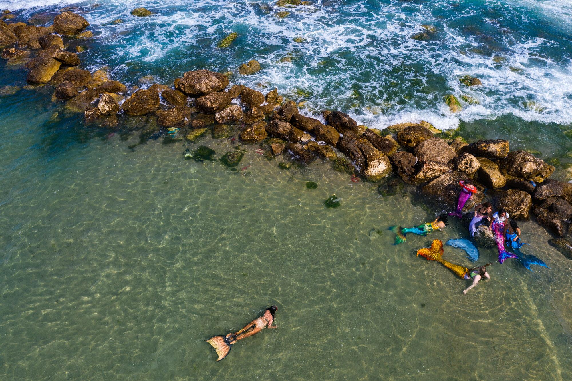 Members of the Israeli Mermaid Community swim with mermaid tails at the beachfront in Bat Yam, near Tel Aviv, Israel, on May 23, 2020. (AP Photo/Oded Balilty)