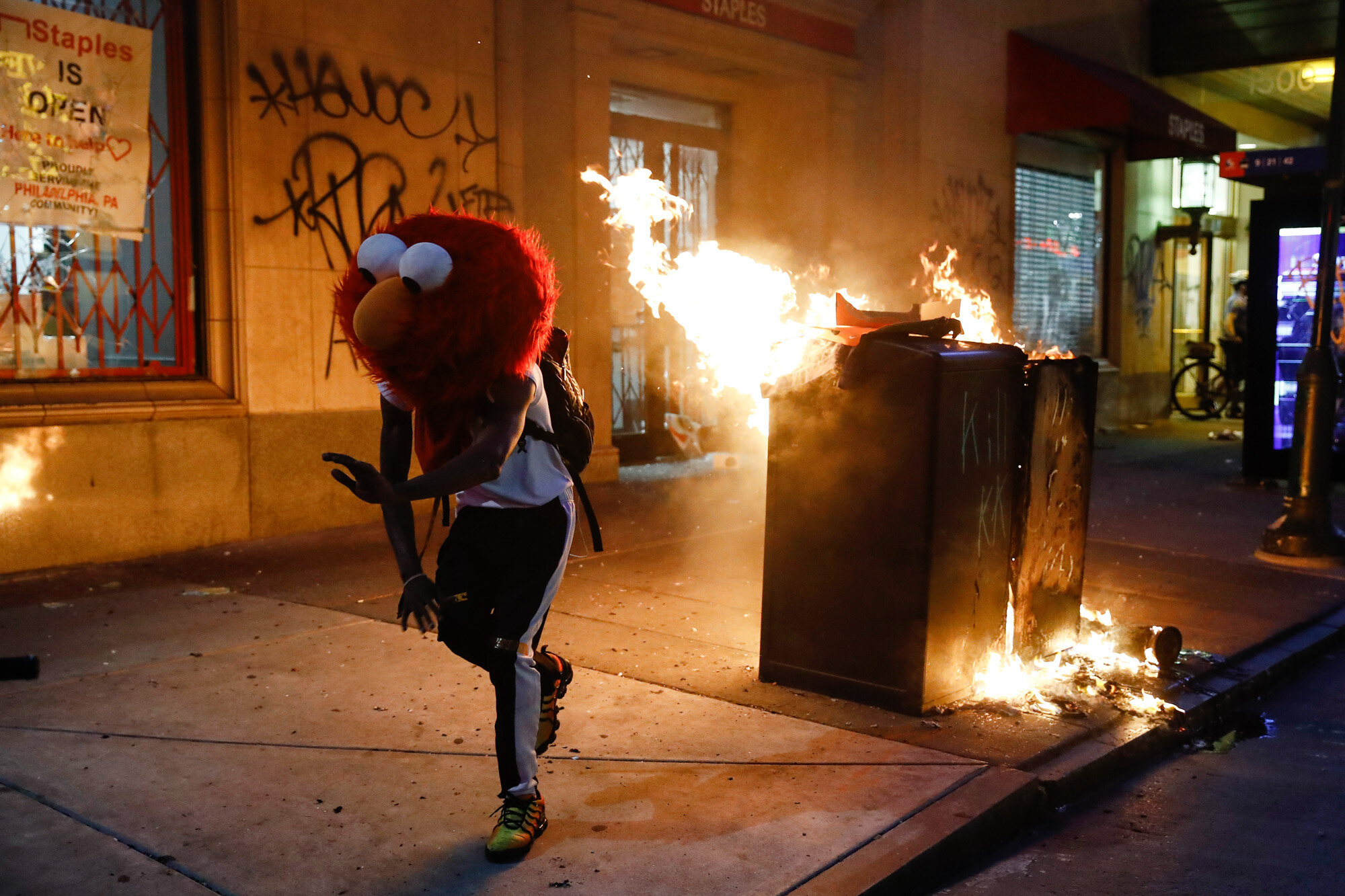 A protester in an Elmo mask dances as a street fire burns on May 30, 2020, during a protest in Philadelphia over the death of George Floyd, a Black man who was killed while in police custody in Minneapolis on May 25. (AP Photo/Matt Rourke)