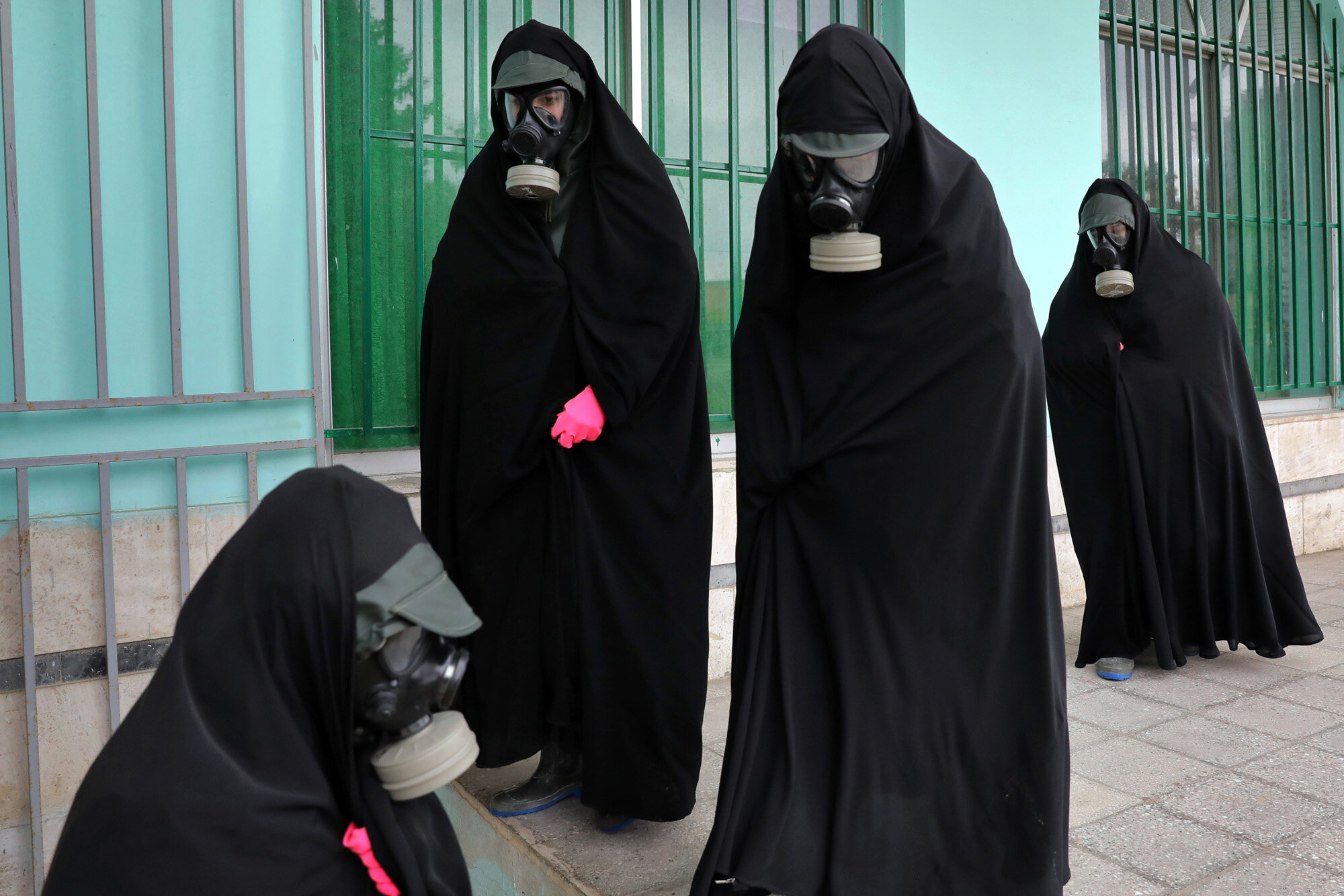 """Women clerics wearing protective clothing and """"chador,"""" a head-to-toe garment, arrive at a cemetery to prepare the body of a person who died from COVID-19 for a funeral, in Ghaemshahr, Iran, on April 30, 2020. (AP Photo/Ebrahim Noroozi)"""