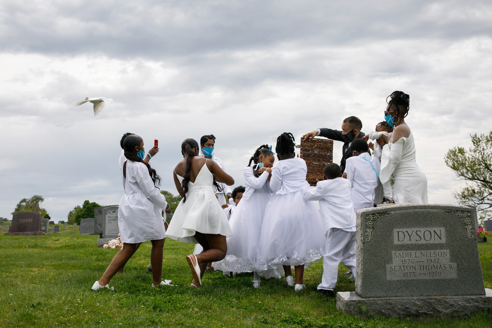 Grandchildren of Joanne Paylor, of southwest Washington, react to doves released during the interment ceremony for Paylor at Lincoln Memorial Cemetery in Suitland-Silver Hill, Md. on May 3, 2020. Although Paylor did not die from the coronavirus, almost every aspect of her funeral was affected by the pandemic. (AP Photo/Jacquelyn Martin)