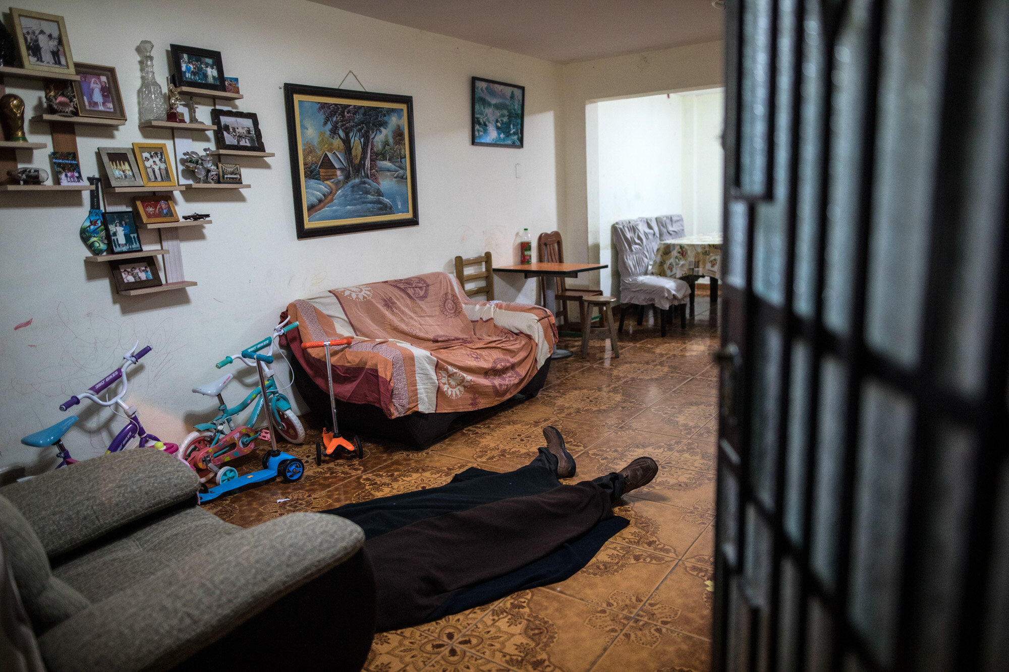 The body of Ricardo Noriega, 77, lies on the floor of his living room in Lima, Peru, on May 4, 2020, after he died of COVID-19. Noriega had great difficulty in breathing, one of the most characteristic symptoms of the disease, and waited for death sitting in an armchair in the living room after he was unable to find a taxi to take him to the hospital that morning. (AP Photo/Rodrigo Abd)