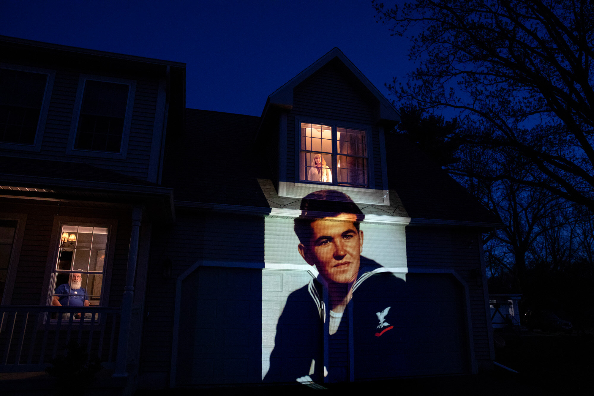 An image of U.S. Navy veteran Stephen Kulig is projected onto the home of his daughter, Elizabeth DeForest, as she looks out the window of a spare bedroom while her husband, Kevin, sits downstairs, in Chicopee, Mass., on May 3, 2020. Kulig, a resident of the Soldier's Home in Holyoke, Mass., died from COVID-19 at the age of 92. (AP Photo/David Goldman)