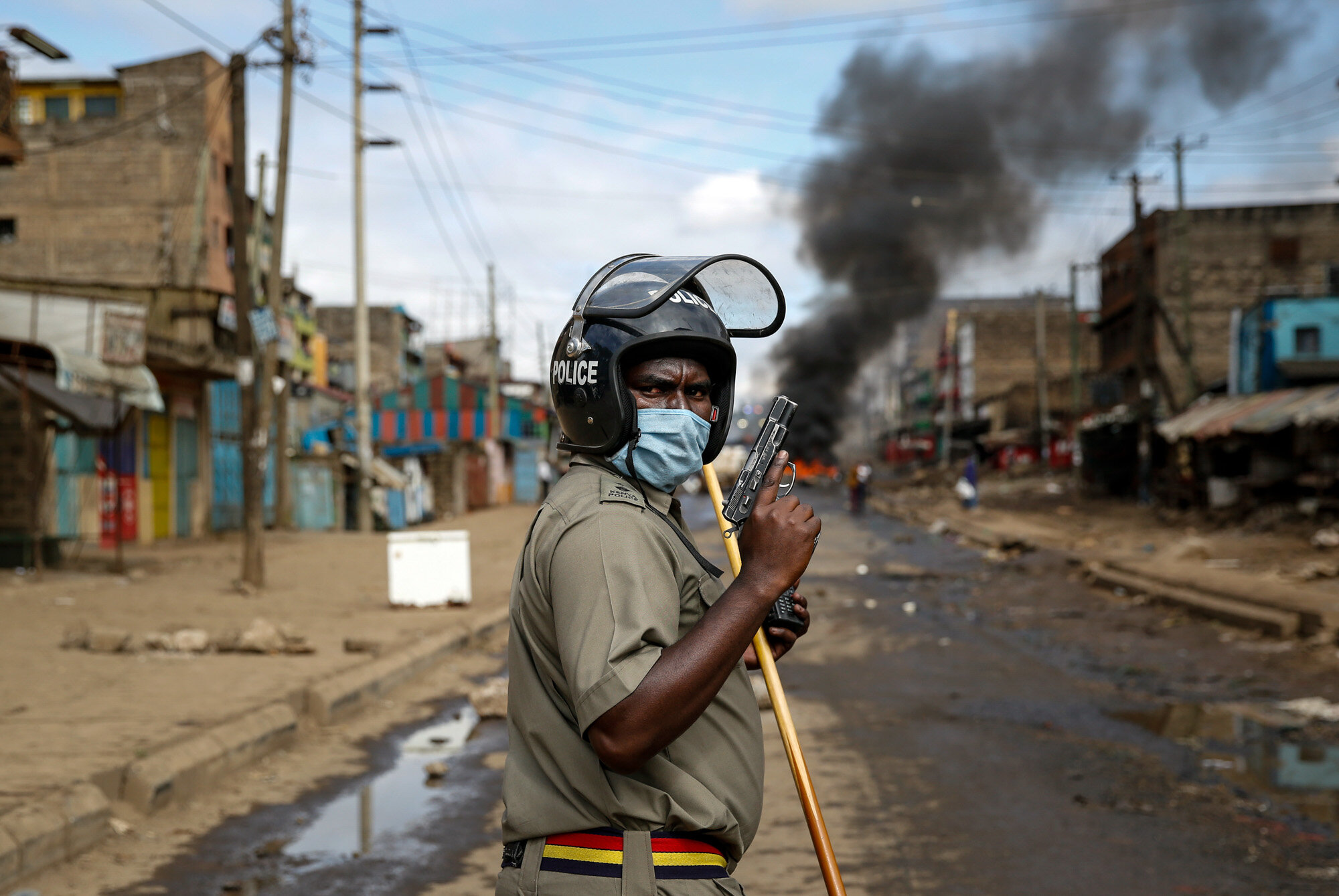 A police officer holds a pistol during clashes with protesters near a barricade of burning tires in the Kariobangi slum of Nairobi, Kenya, on May 8, 2020. Hundreds of protesters blocked one of the capital's major highways to protest government demolitions of the homes of more than 7,000 people, causing many to sleep out in the rain and cold because of restrictions on movement due to the coronavirus. (AP Photo/Brian Inganga)