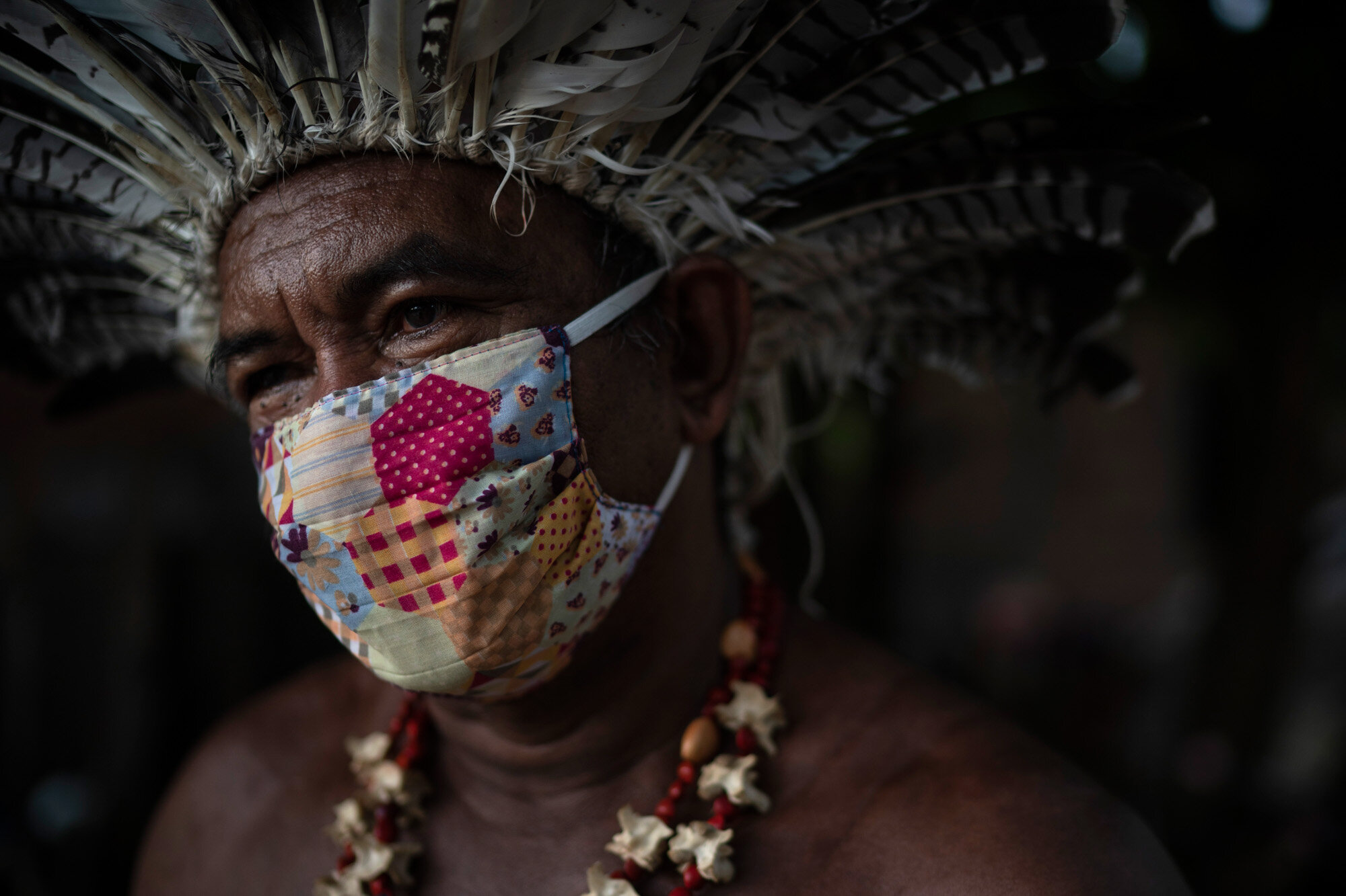 """Cacique Pedro poses for a photo as he sits outside his house in the """"Park of Indigenous Nations"""" community in Manaus, Brazil, on May 10, 2020. (AP Photo/Felipe Dana)"""