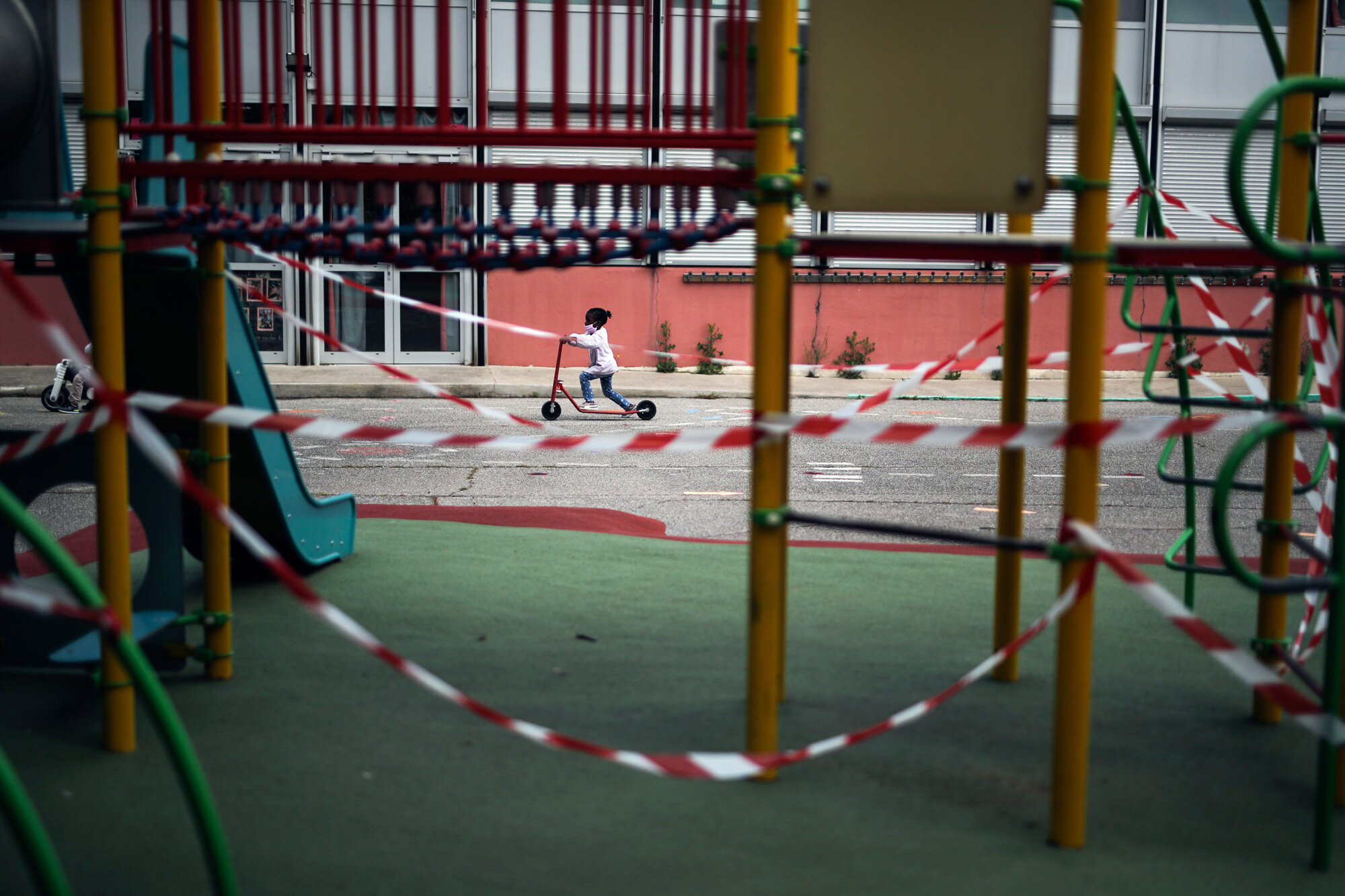 A girl rides a scooter past the Saint-Tronc Castelroc primary school playground, closed to prevent the spread of the coronavirus, in Marseille, France, on May 14, 2020. (AP Photo/Daniel Cole)