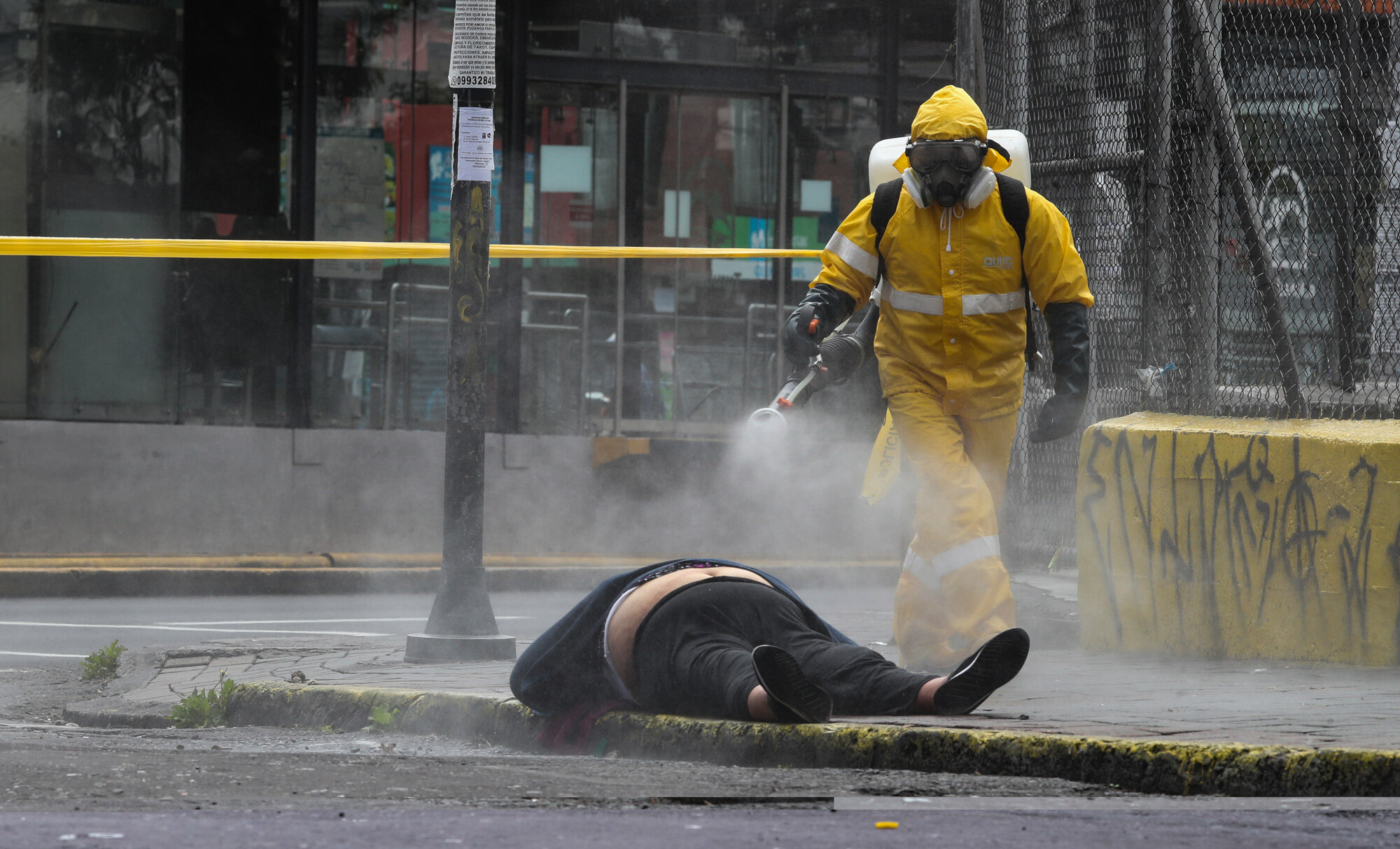 A worker from the city's forensic department  in Quito, Ecuador, sprays disinfectant over the body of a woman who died on the street on May 14, 2020. Forensic workers at the scene conducted a COVID-19 rapid test and said the woman tested negative. (AP Photo/Dolores Ochoa)