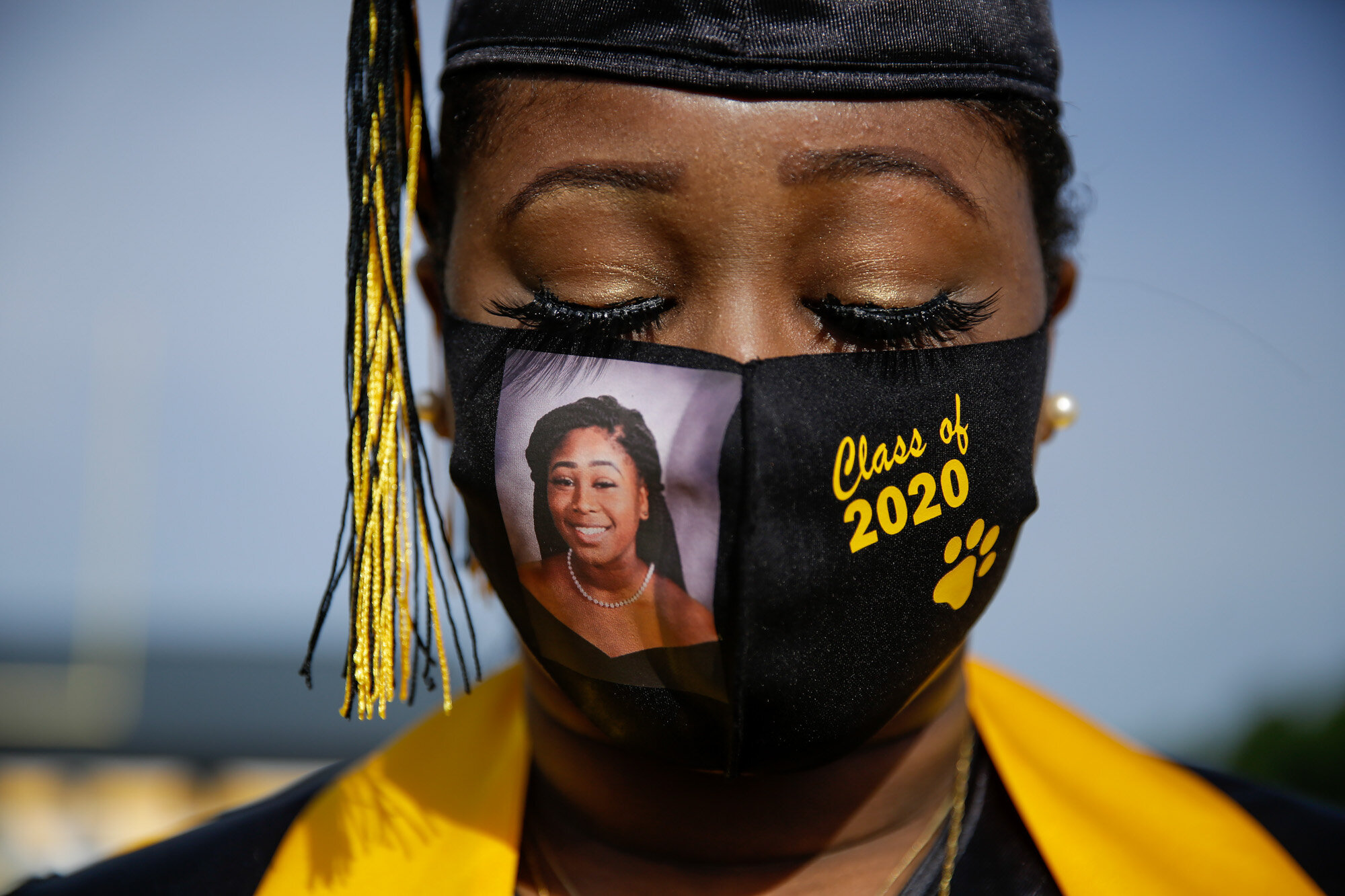 """Yasmine Protho, 18, wears a photo of herself and """"Class of 2020"""" on her protective mask amid the COVID-19 virus outbreak as she graduates with only nine other classmates and limited family attending at Chattahoochee County High School in Cusseta, Ga., on May 15, 2020. (AP Photo/Brynn Anderson)"""
