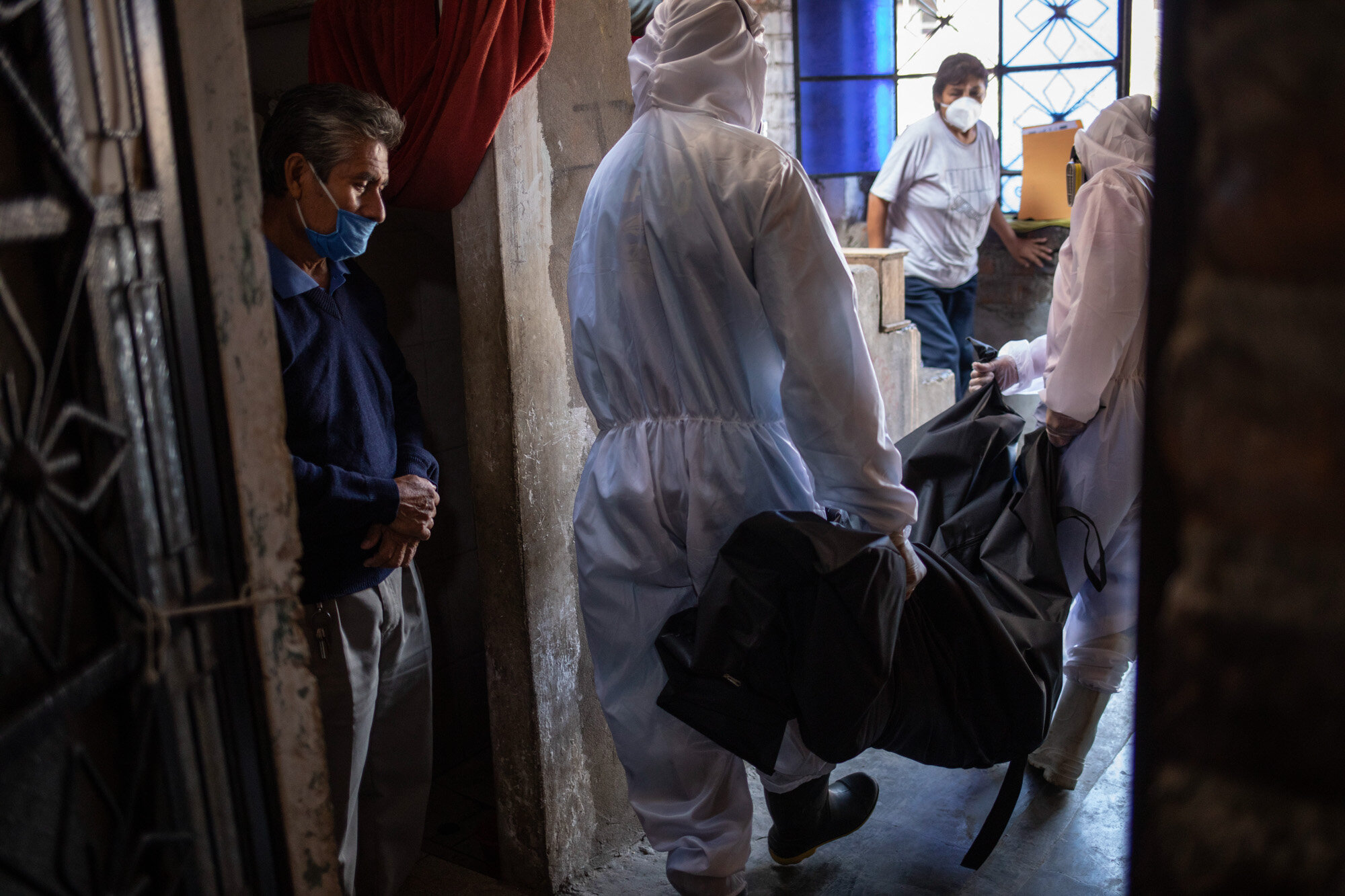 Teodoro Mejia, left, watches workers from the Piedrangel funeral home remove the body of his wife, Berta Cusi Palomino, from their home in Lima, Peru, May 14, 2020. Palomino was believed to have died from COVID-19. (AP Photo/Rodrigo Abd)
