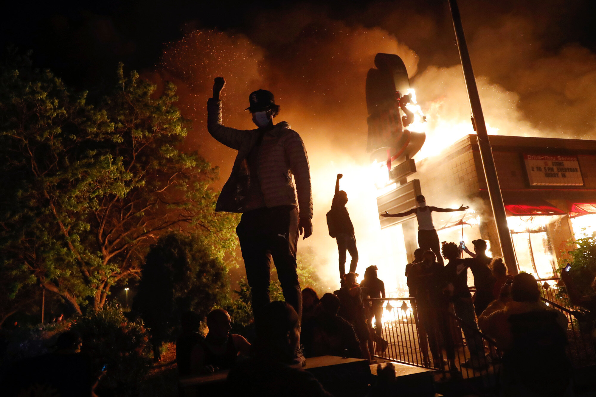 People demonstrate outside a burning Arby's fast food restaurant on May 29, 2020, in Minneapolis during a protest over the death of George Floyd, a Black man who died after a white Minneapolis police officer pressed a knee into his neck for several minutes. (AP Photo/John Minchillo)