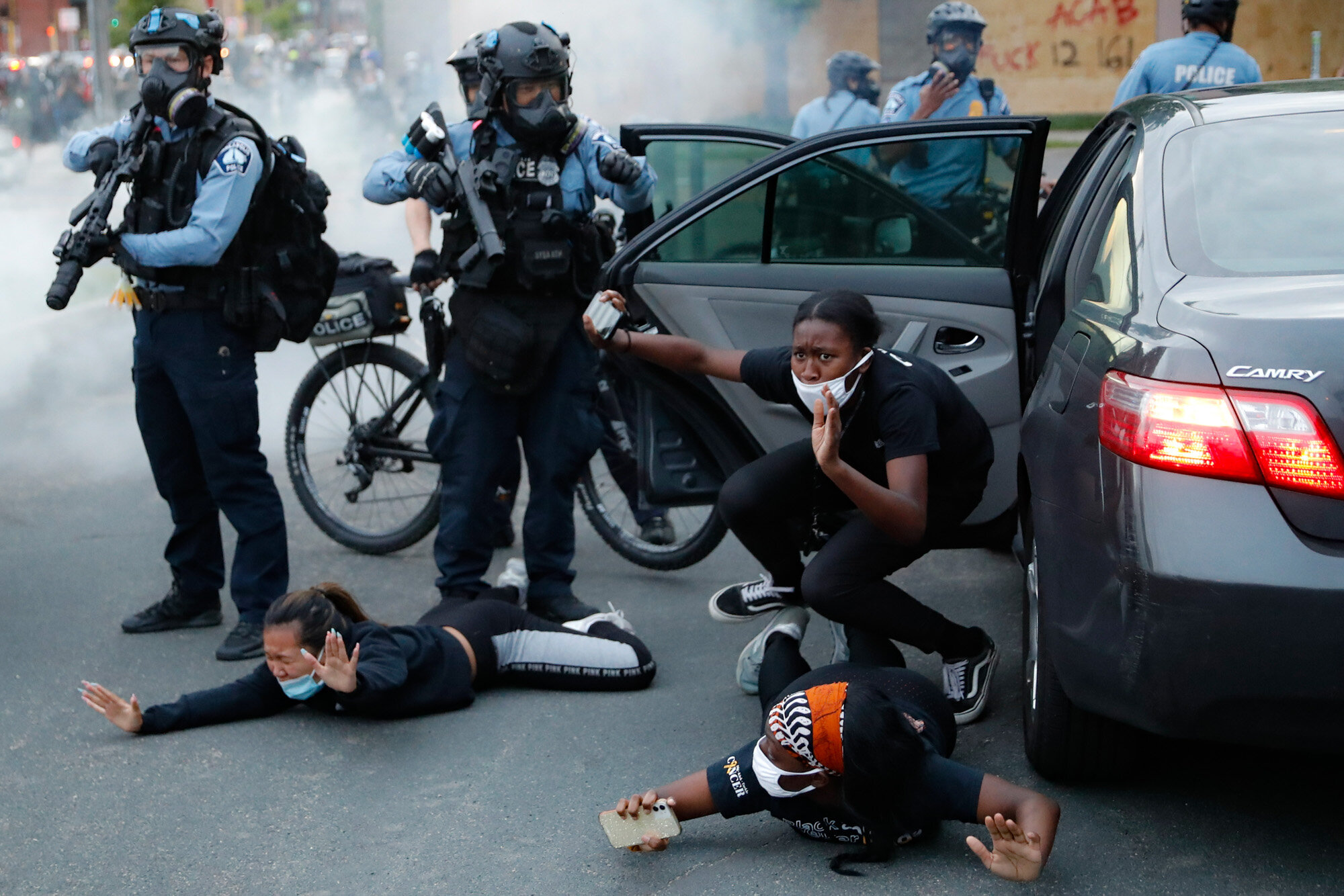 Motorists are ordered to the ground from their vehicle by police on May 31, 2020, during a protest in Minneapolis over the death of George Floyd, a Black man who died after a white Minneapolis police officer pressed a knee into his neck for several minutes. (AP Photo/John Minchillo)