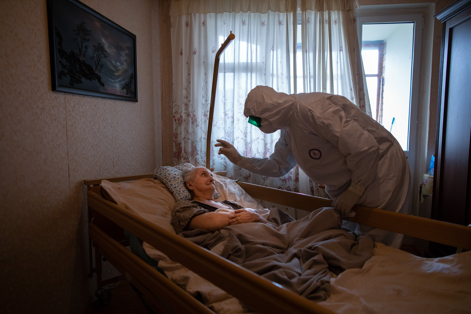 Father Vasily Gelevan, a Russian Orthodox priest, blesses Lyudmila Polyak, 86, who is believed to be suffering from COVID-19, at her apartment in Moscow. (AP Photo/Alexander Zemlianichenko)