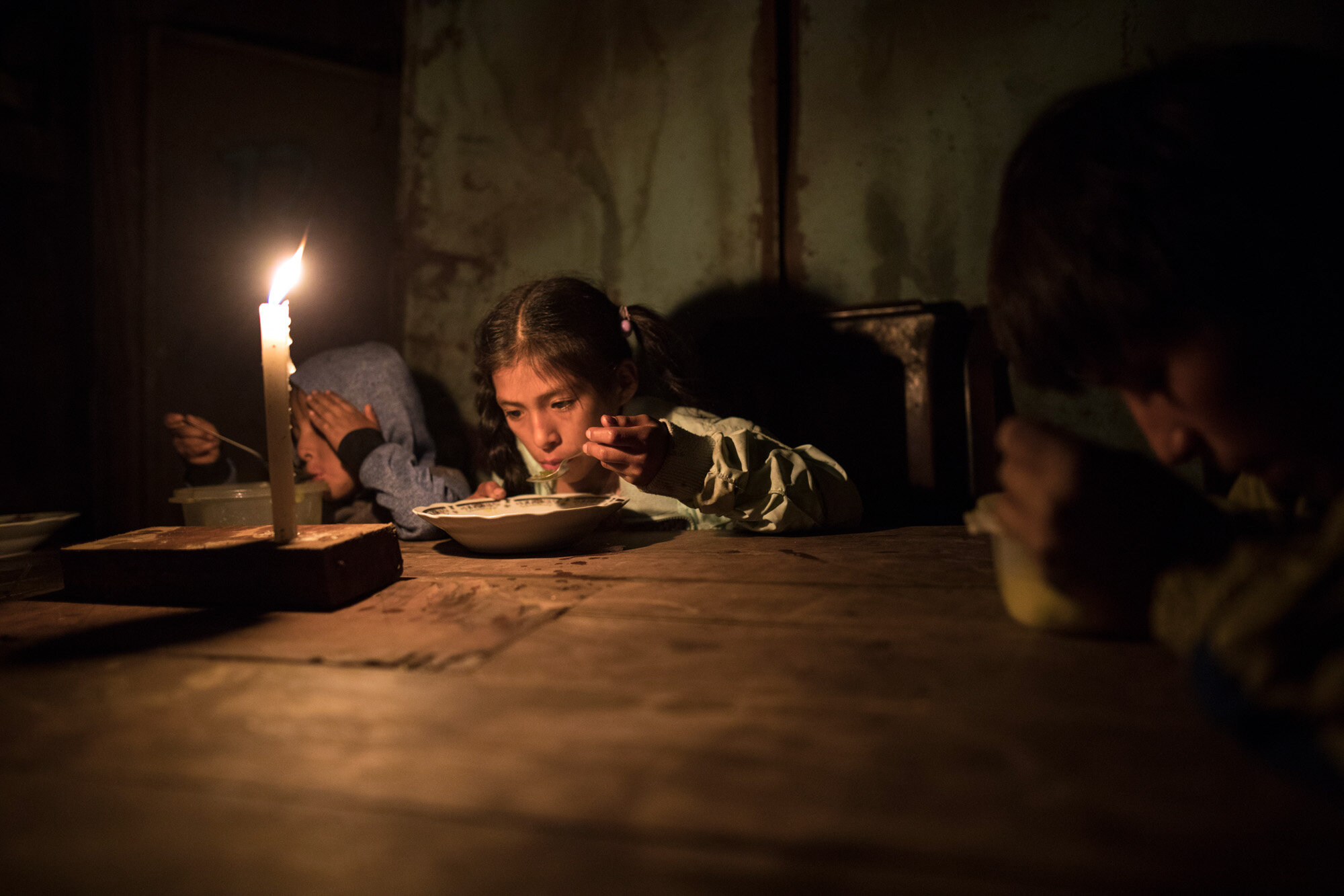 Siblings, from left, Estiben, Estefany and Javier Aquino eat dinner illuminated by a candle in their home in the Nueva Esperanza neighborhood, which has no access to electricity, in Lima, Peru, on June 8, 2020. (AP Photo/Rodrigo Abd)