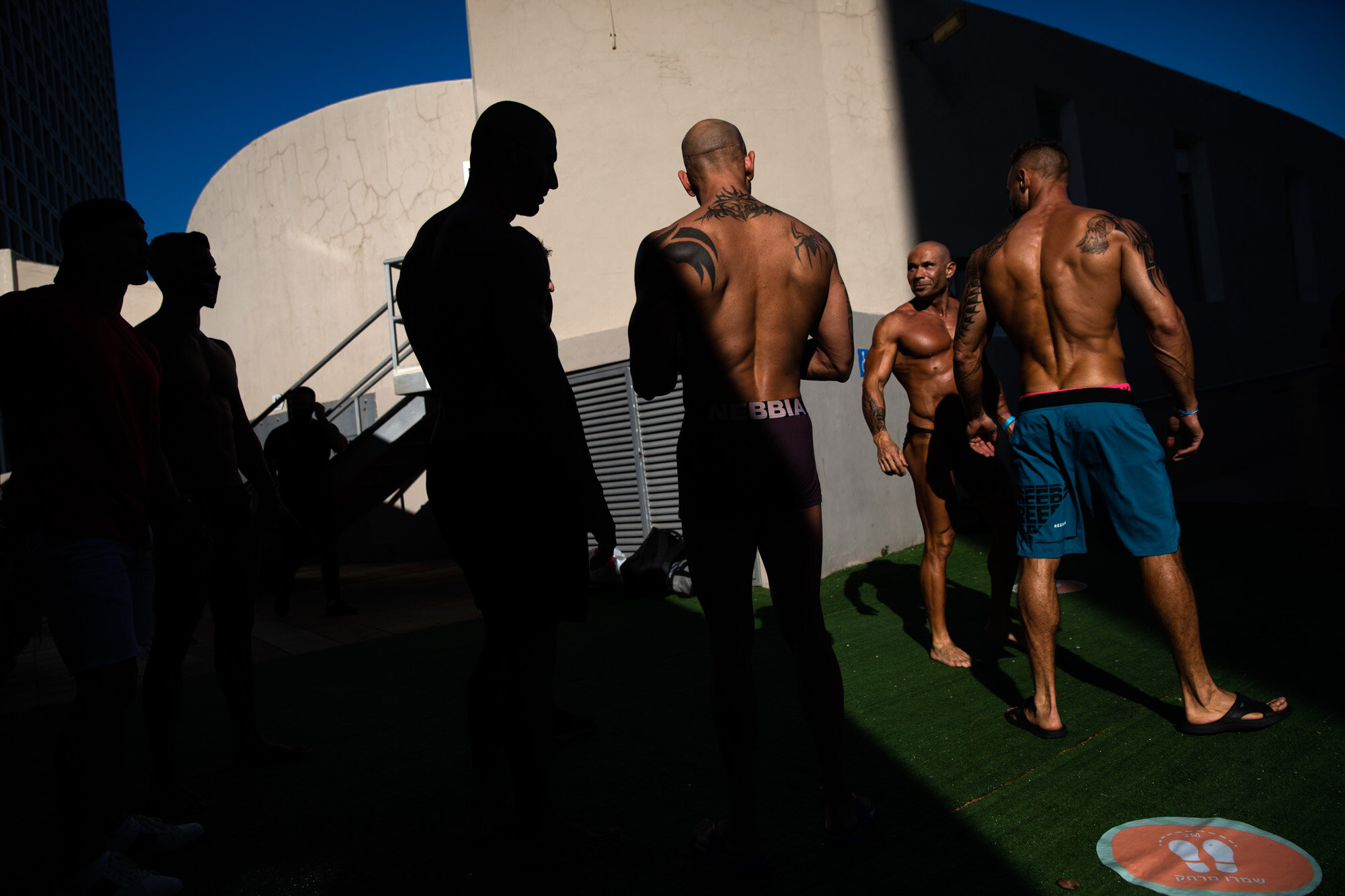 Contestants exercise backstage during the National Amateur Body Builders Association competition in Tel Aviv, Israel, on Aug. 19, 2020. Because of the coronavirus pandemic, this year's competition was staged outdoors and the 85 participants were required to don protective masks in line with health codes.  (AP Photo/Oded Balilty)
