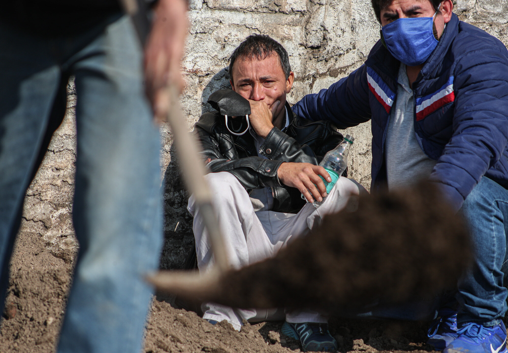 Peruvian migrant Jose Collantes cries as cemetery workers bury his wife Silvia Cano, who he says died of COVID-19, at a Catholic cemetery in Santiago, Chile, on July 3, 2020. Collantes said he preferred to cremate her in order to take the ashes home with him but, due to bureaucracy, had already been waiting two weeks. (AP Photo/Esteban Felix)