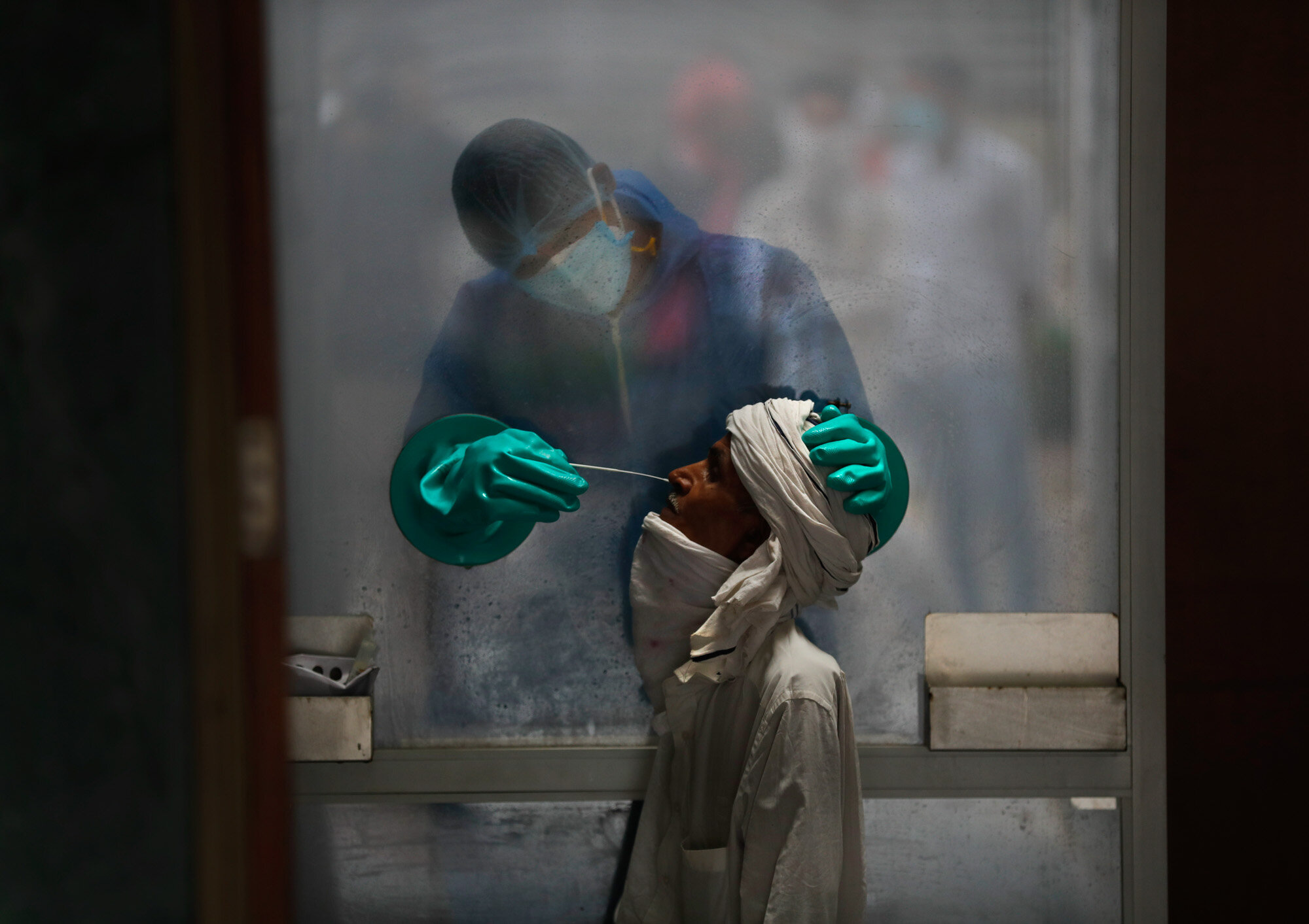 A health worker takes a nasal swab of a person for a COVID-19 test at a hospital in New Delhi, India, on July 6, 2020. (AP Photo/Manish Swarup)