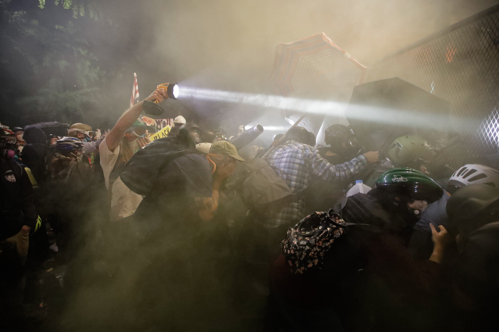 Demonstrators push on a fence as tear gas is deployed during a Black Lives Matter protest at the Mark O. Hatfield United States Courthouse in Portland, Ore., on July 25, 2020. (AP Photo/Marcio Jose Sanchez)