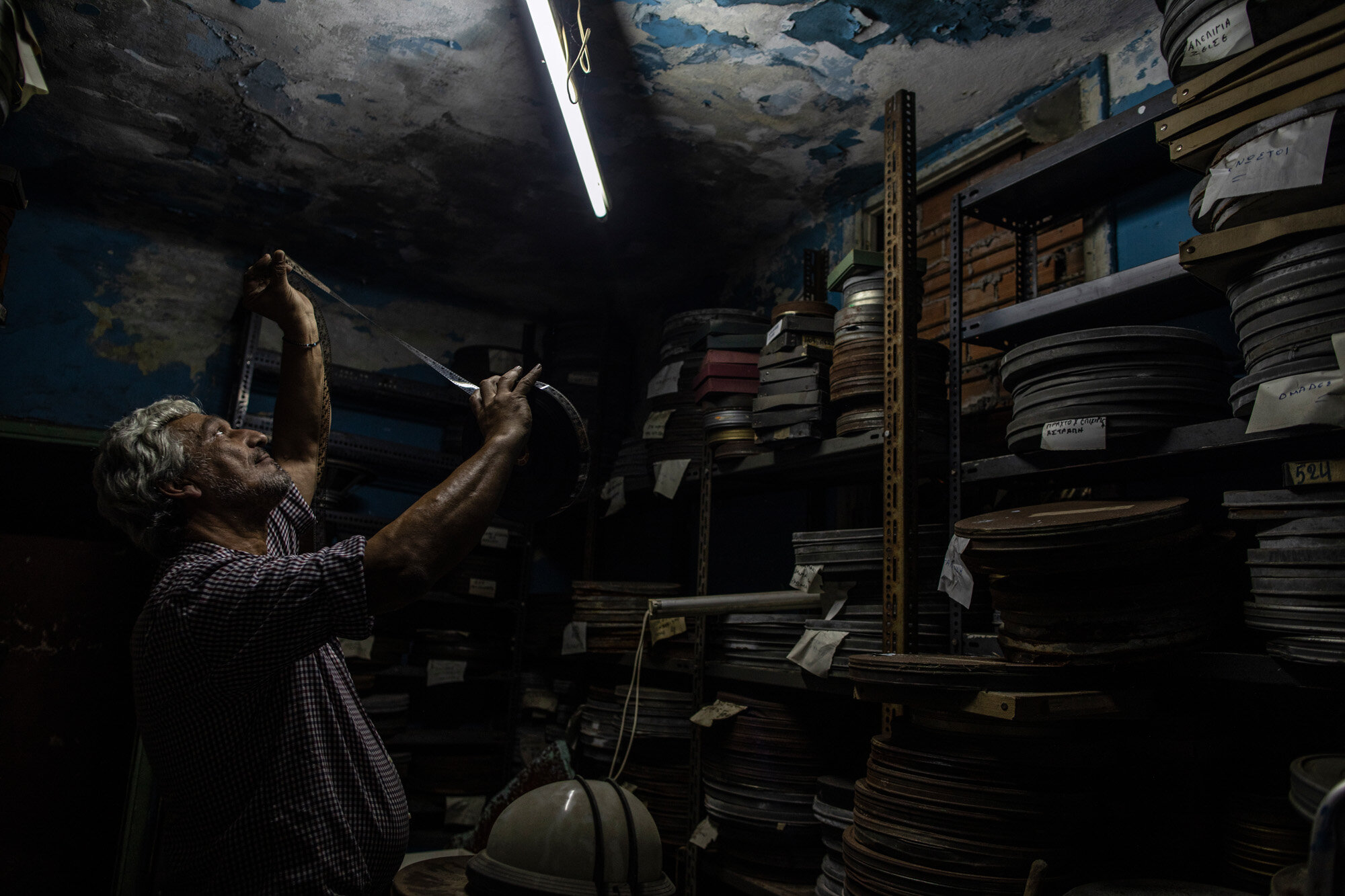 Projector operator Pavlos Lepeniotis checks the quality of movie film inside a warehouse at the Zephyros open-air cinema, which specializes in films from past decades, in Ano Petralona, central Athens, on June 3, 2020. Lepeniotis has worked in movie theaters since age 12. (AP Photo/Petros Giannakouris)