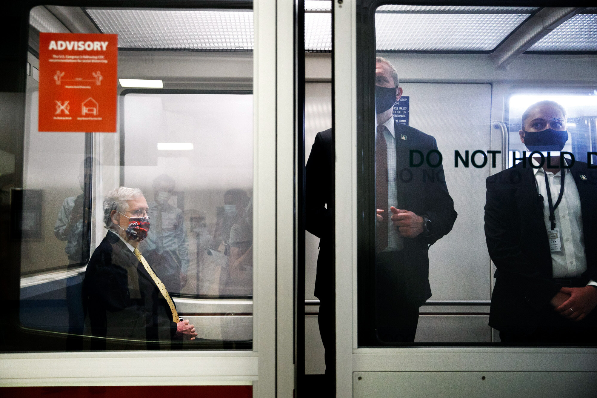 Senate Majority Leader Mitch McConnell of Kentucky, left, wears a mask for protection against the coronavirus, along with members of security, as he rides the Senate Subway between meetings on Capitol Hill in Washington on July 21, 2020. (AP Photo/Jacquelyn Martin)