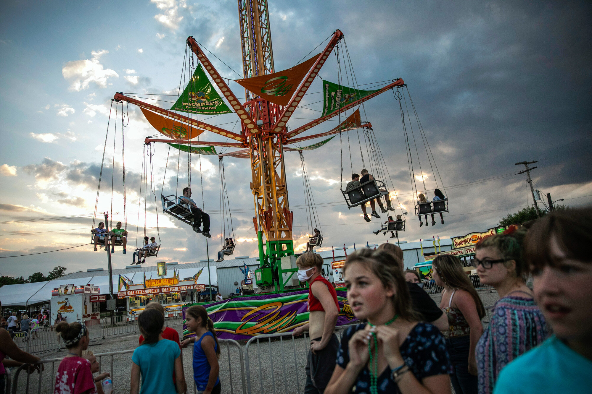 People wait to ride a revolving swing at the Perry State Fair in New Lexington, Ohio, on July 24, 2020. (AP Photo/Wong Maye-E)