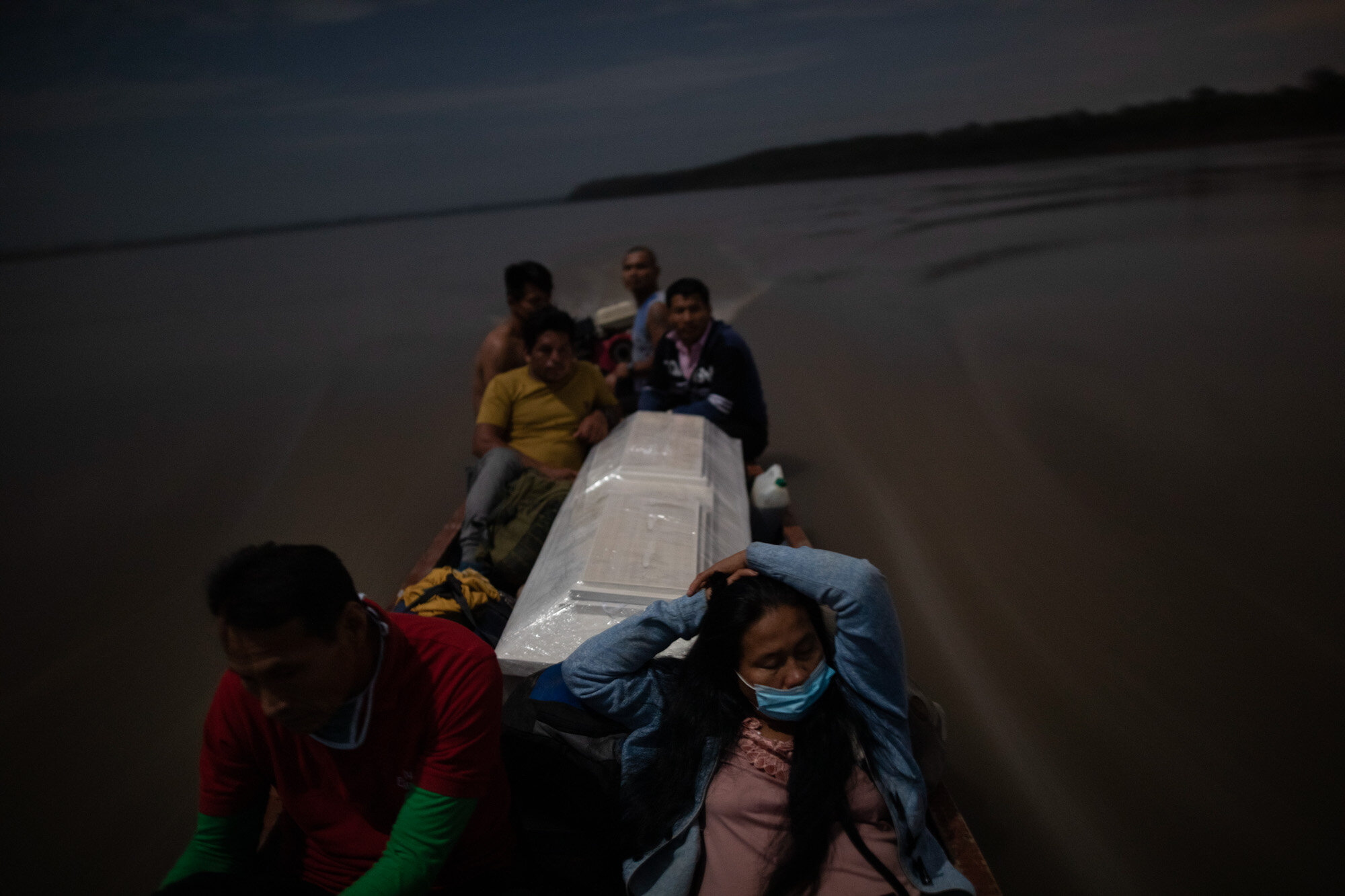 Relatives accompany the coffin that contains the remains of Jose Barbaran, who is believed to have died from complications related to the coronavirus, as they travel by boat on Peru's Ucayali River on Sept. 29, 2020. Despite the risk, family members decided to travel by night to Barbaran's hometown of Palestina, a four-hour journey. (AP Photo/Rodrigo Abd)