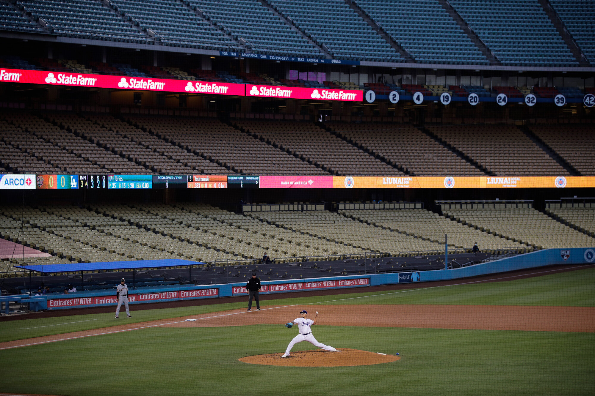 With the seats at Dodger Stadium empty, Los Angeles Dodgers starting pitcher Julio Urias throws to a San Francisco Giants batter during the third inning of a baseball game on July 26, 2020, in Los Angeles. (AP Photo/Jae C. Hong)