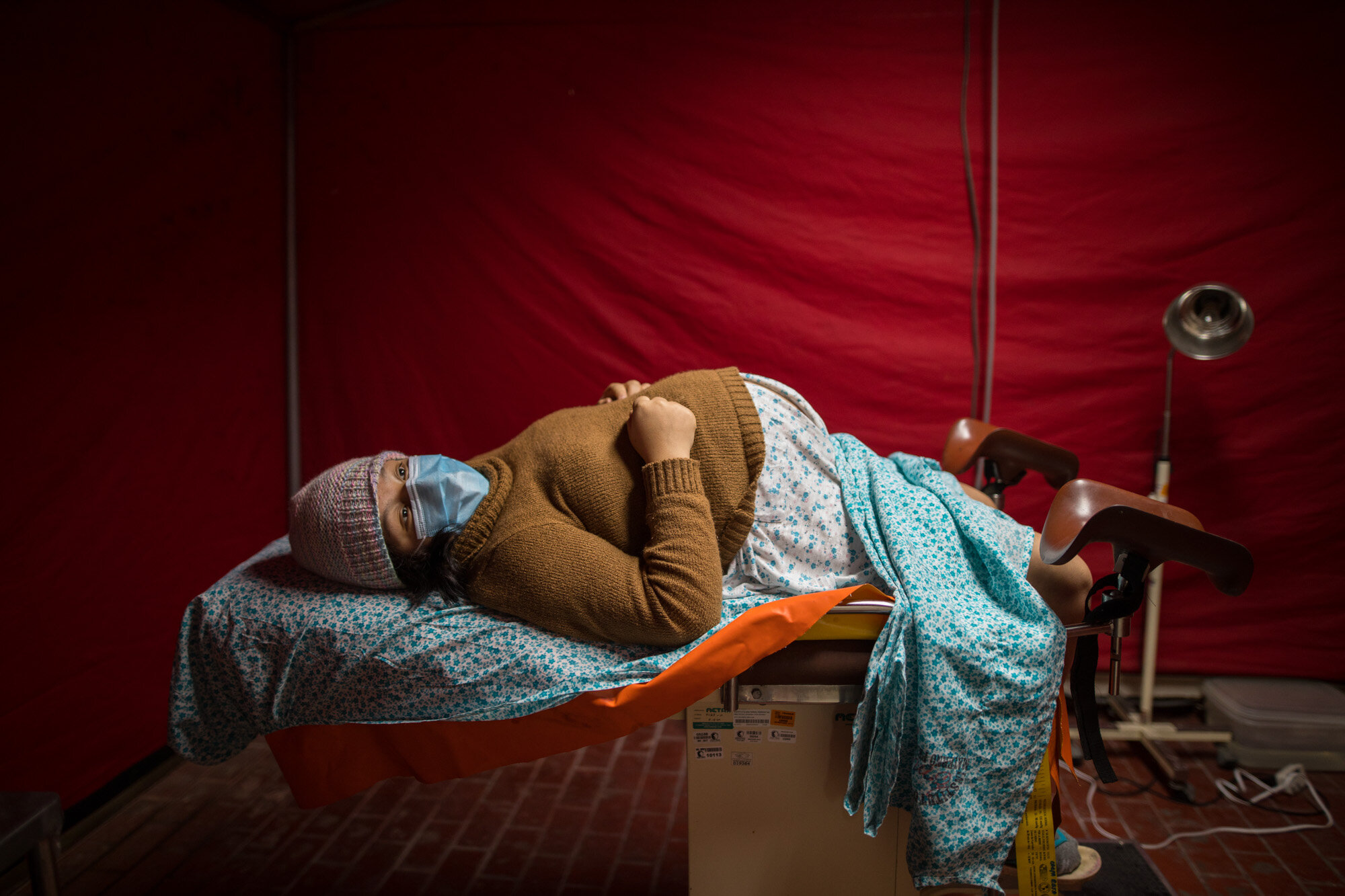 Olinda Tafur, 20, lies on an examination table as she waits to be seen by an obstetrician inside a tent set up in the emergency area of the National Perinatal and Maternal Institute to receive women in labor who are infected with COVID-19, in Lima, Peru, on July 29, 2020. Just before giving birth to her first child, Tafur learned that she had tested positive for the new coronavirus upon arriving with labor pains to the emergency area of the Institute. (AP Photo/Rodrigo Abd)