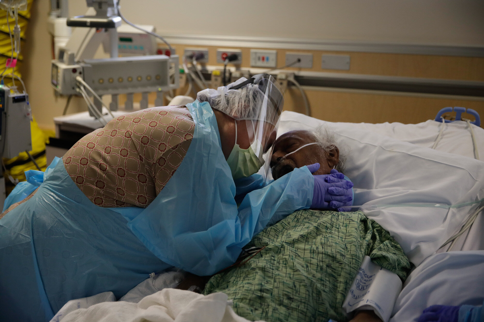 Romelia Navarro, 64, weeps while hugging her husband, Antonio, in his final moments in a COVID-19 unit at St. Jude Medical Center in Fullerton, Calif., on July 31, 2020. (AP Photo/Jae C. Hong)