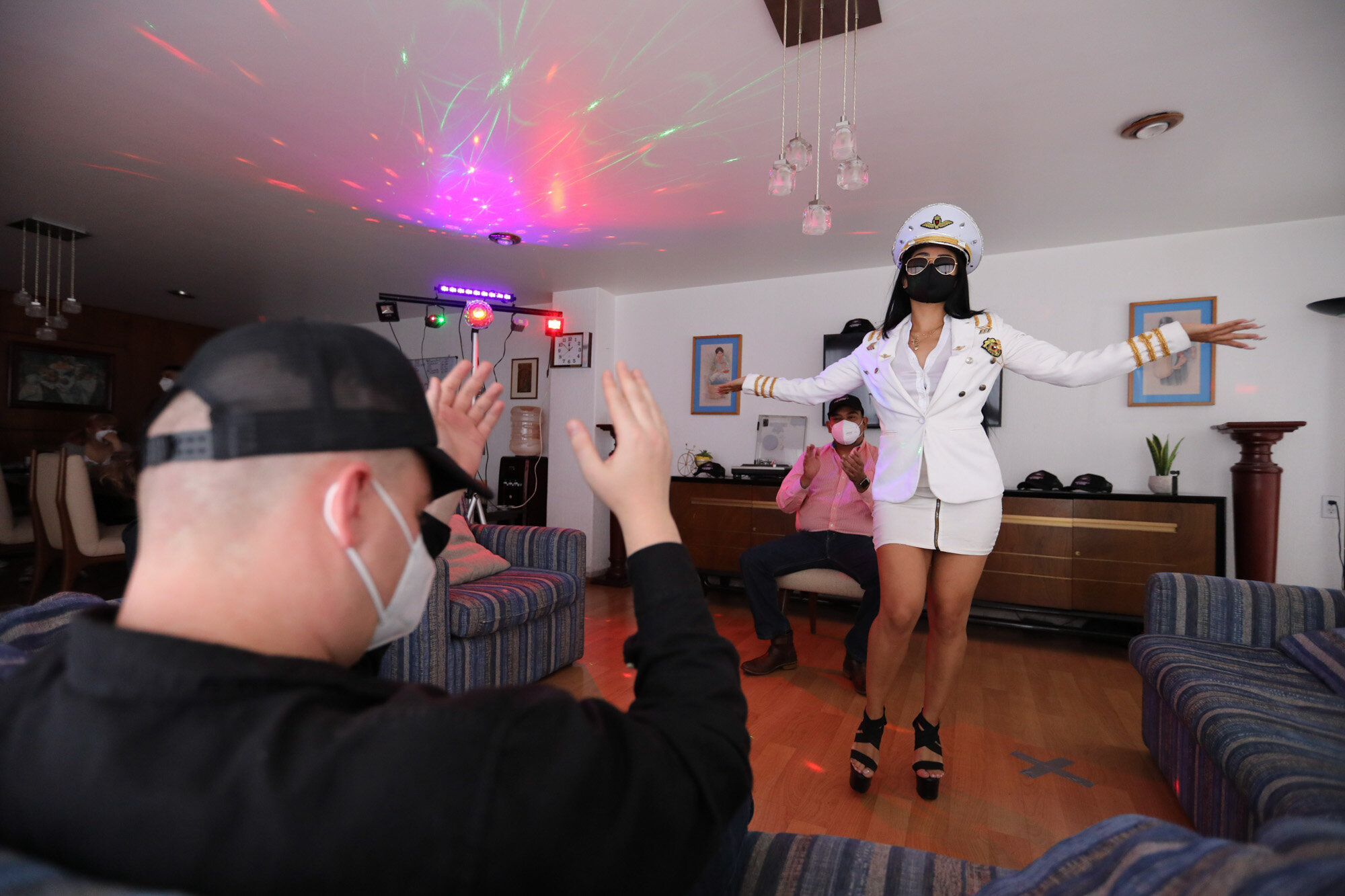 A woman wearing a protective face mask amid the coronavirus pandemic dances in a client's home in Mexico City on Aug. 8, 2020. The pandemic has forced businesses to adapt to a new normality and the adult entertainment industry is no exception. (AP Photo/Eduardo Verdugo)