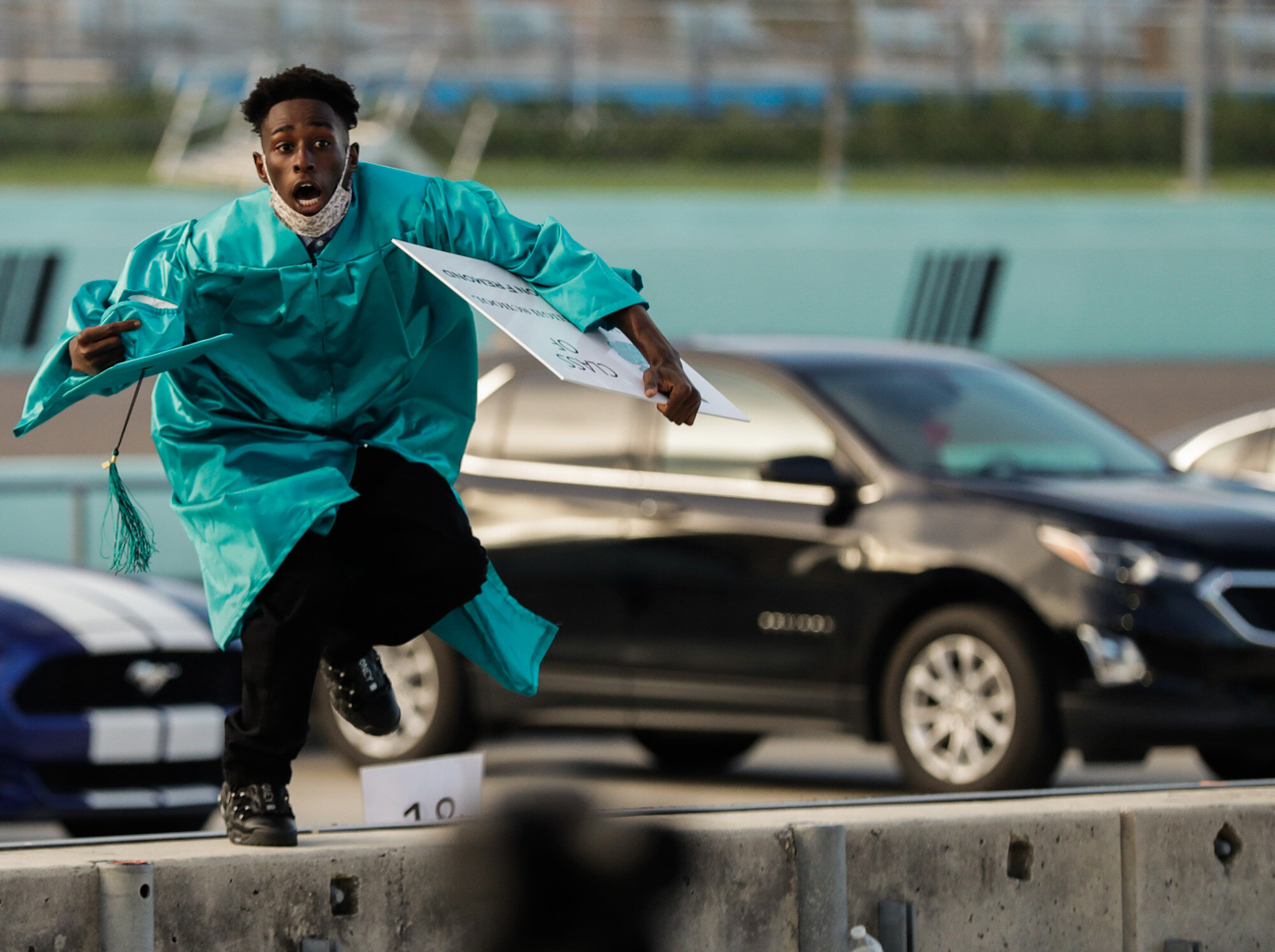 Richardson Fremond leaps over a wall as he runs to collect an award during the Chambers High School graduation ceremony at Homestead-Miami Speedway in Homestead, Fla., on June 23, 2020. The ceremony was held at the race track to enable social distancing during the coronavirus pandemic and the 41 seniors who graduated crossed the start-finish line to receive their diplomas. (AP Photo/Wilfredo Lee)