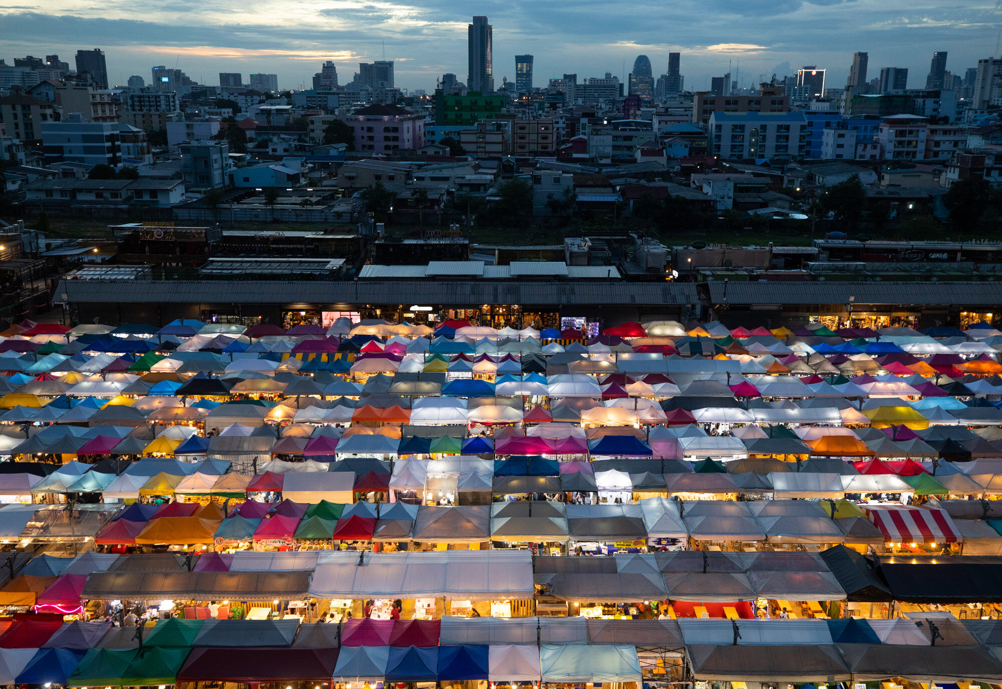 Tents of food stalls and other vendors are illuminated at Rot Fai Market in Bangkok, Thailand, on June 19, 2020, as the government continues to ease restrictions that were imposed to curb the spread of the coronavirus. (AP Photo/Sakchai Lalit)