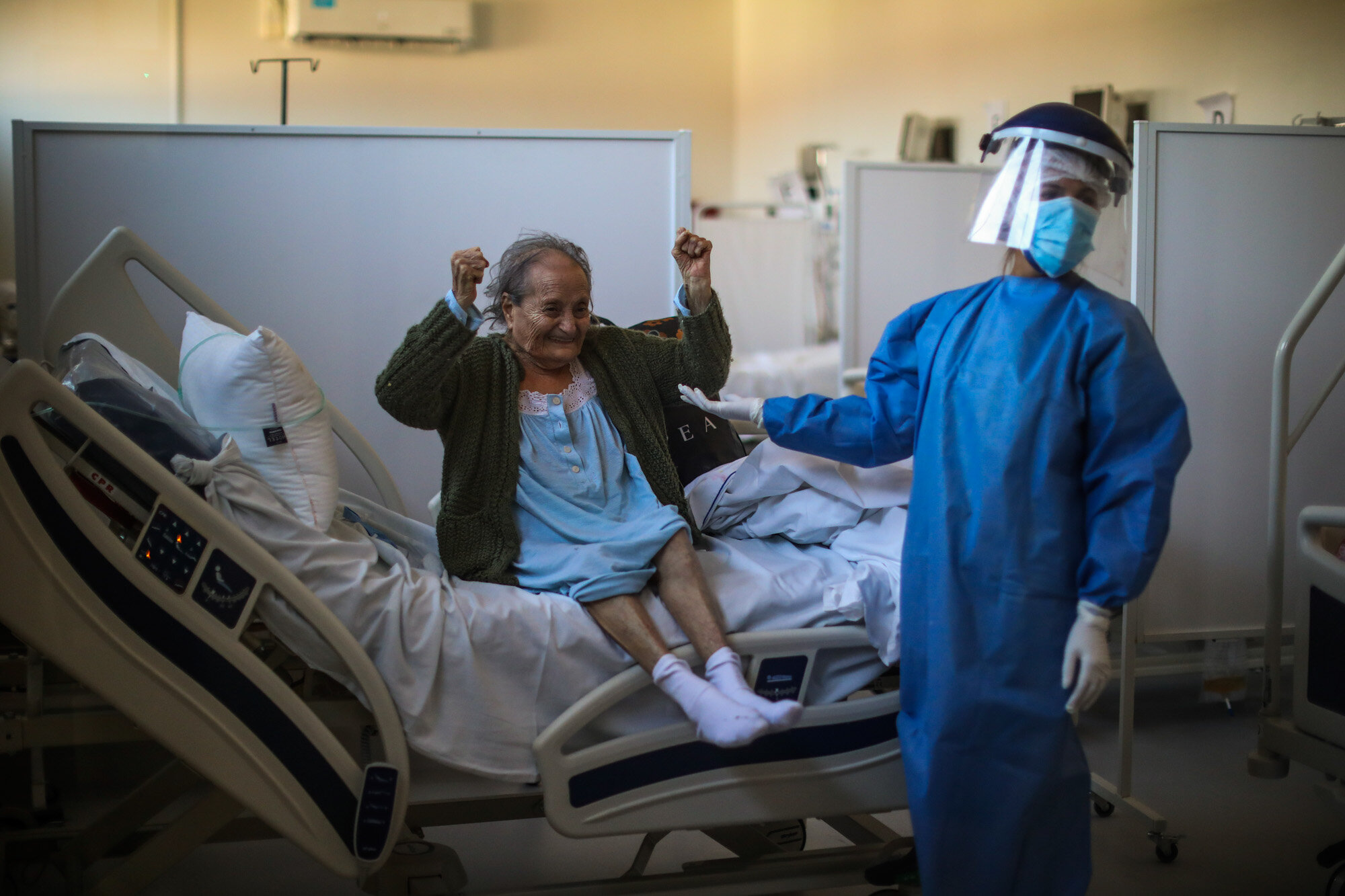 Blanca Ortiz, 84, celebrates after learning from nurses that she will be dismissed from the Eurnekian Ezeiza Hospital, on the outskirts of Buenos Aires, Argentina, on Aug. 13, 2020, several weeks after being admitted with COVID-19. (AP Photo/Natacha Pisarenko)
