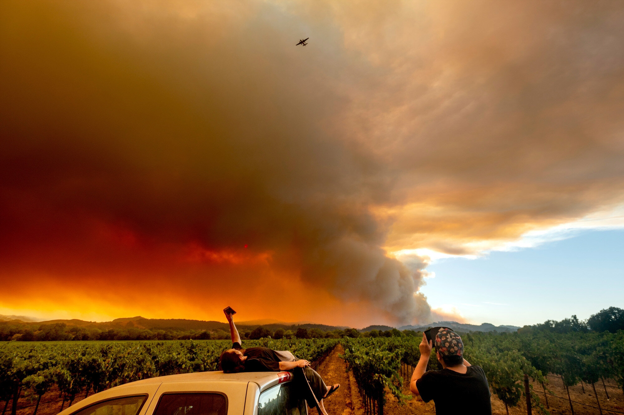 Thomas Henney, left, and Charles Chavira watch a plume of smoke spread over Healdsburg, Calif., as wildfires burn nearby on Aug. 20, 2020. Deadly wildfires in California more than doubled the previous record for the most land burned in a single year in the state. (AP Photo/Noah Berger)