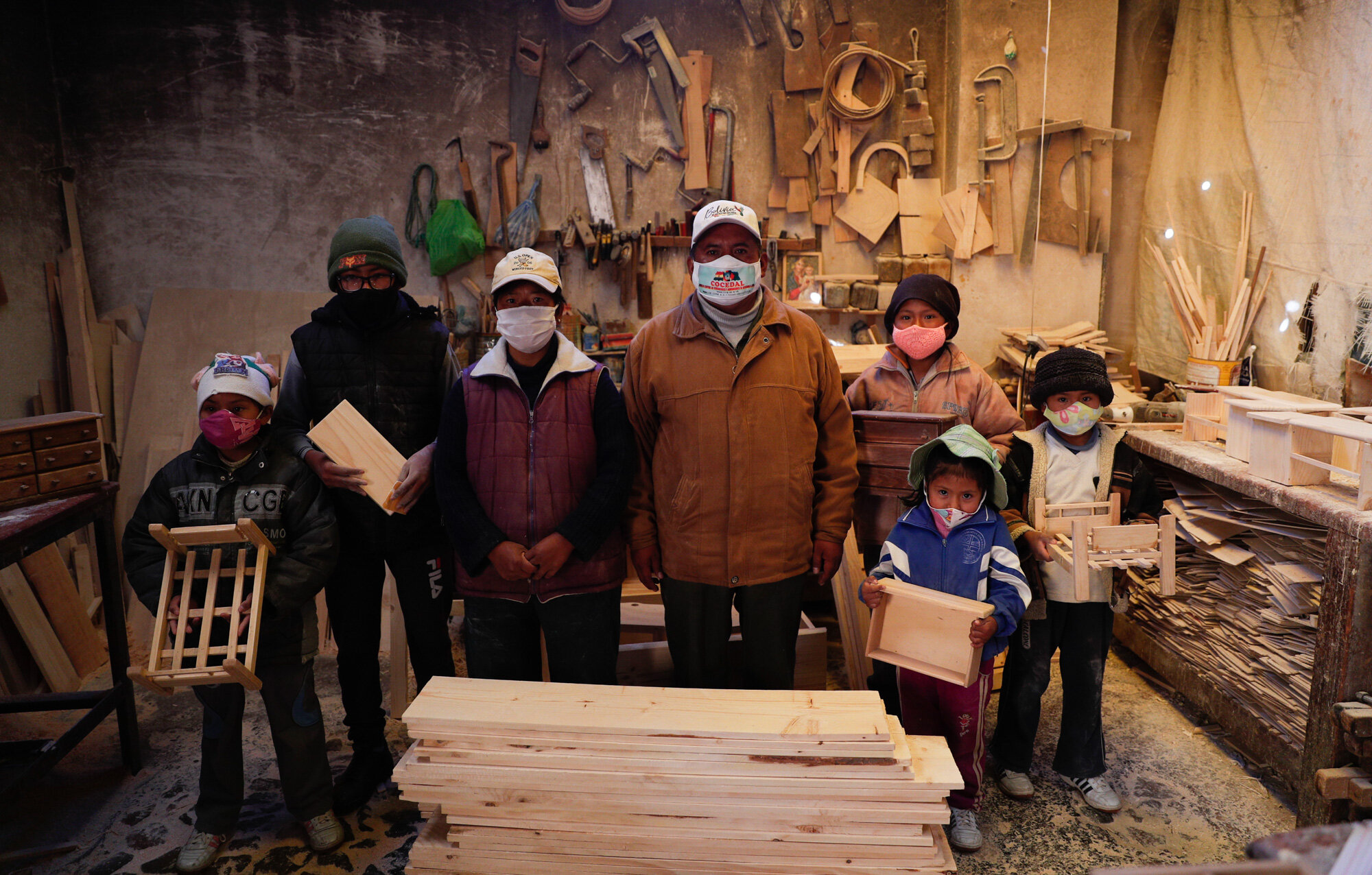 Wearing masks to curb the spread of the coronavirus, the Delgado family poses for a photo in their workshop in El Alto, Bolivia, on Aug. 28, 2020. The five children, from ages 6 and 14, work all day in the family's small carpentry workshop with their parents. (AP Photo/Juan Karita)