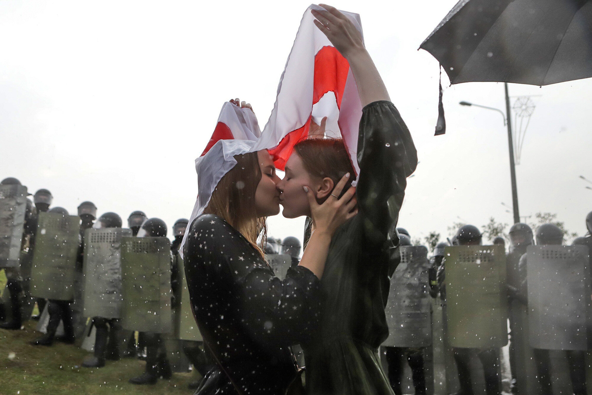 Two women kiss under an old Belarusian national flag as opposition supporters gather near the Independence Palace in Minsk, Belarus, on Aug. 30, 2020. (AP Photo/Nadia Buzhan)