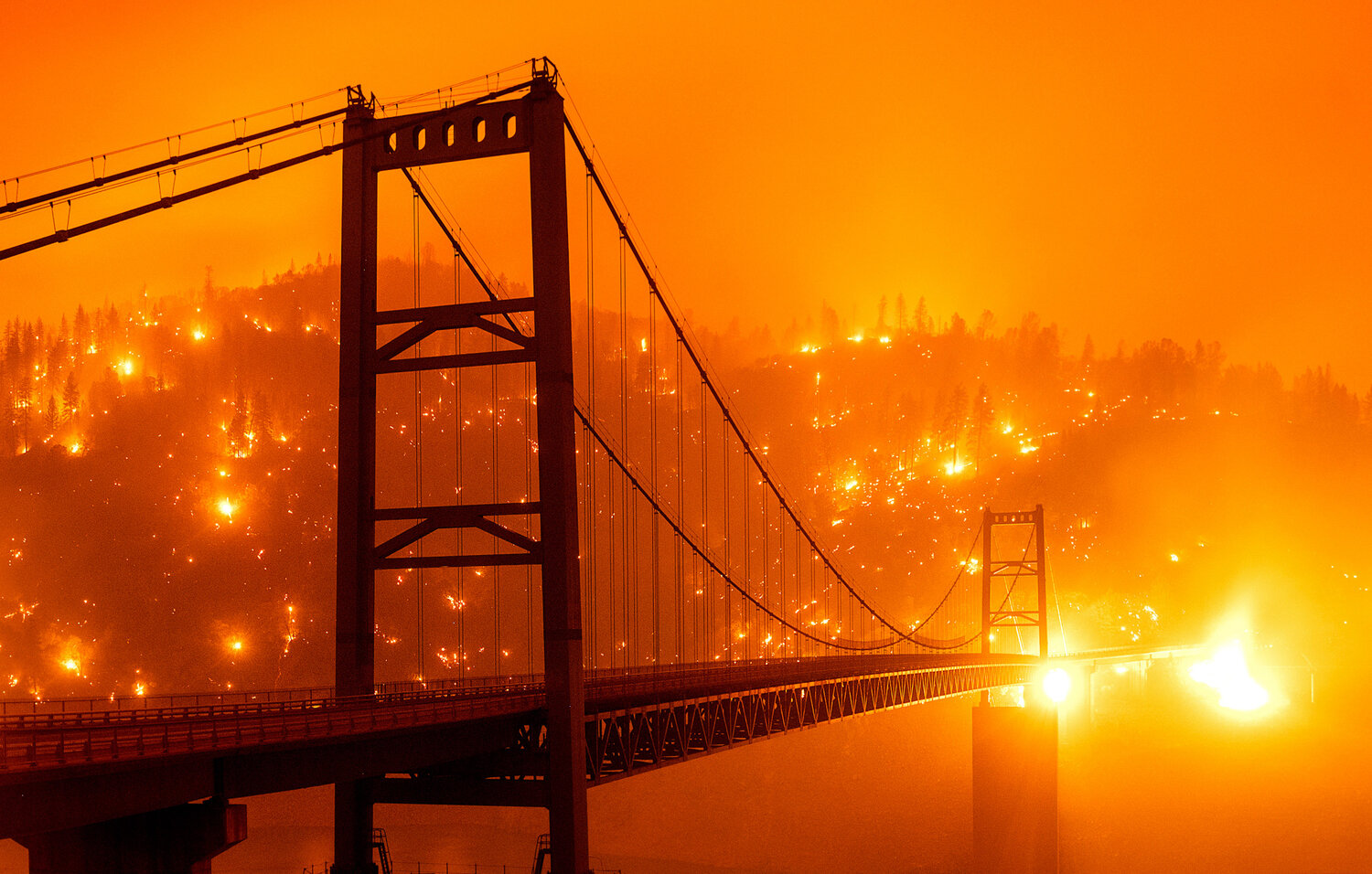 Embers light up a hillside behind the Bidwell Bar Bridge on Sept. 9, 2020, as the Bear Fire burns in Oroville, Calif., in this photo taken with a slow shutter speed. (AP Photo/Noah Berger)