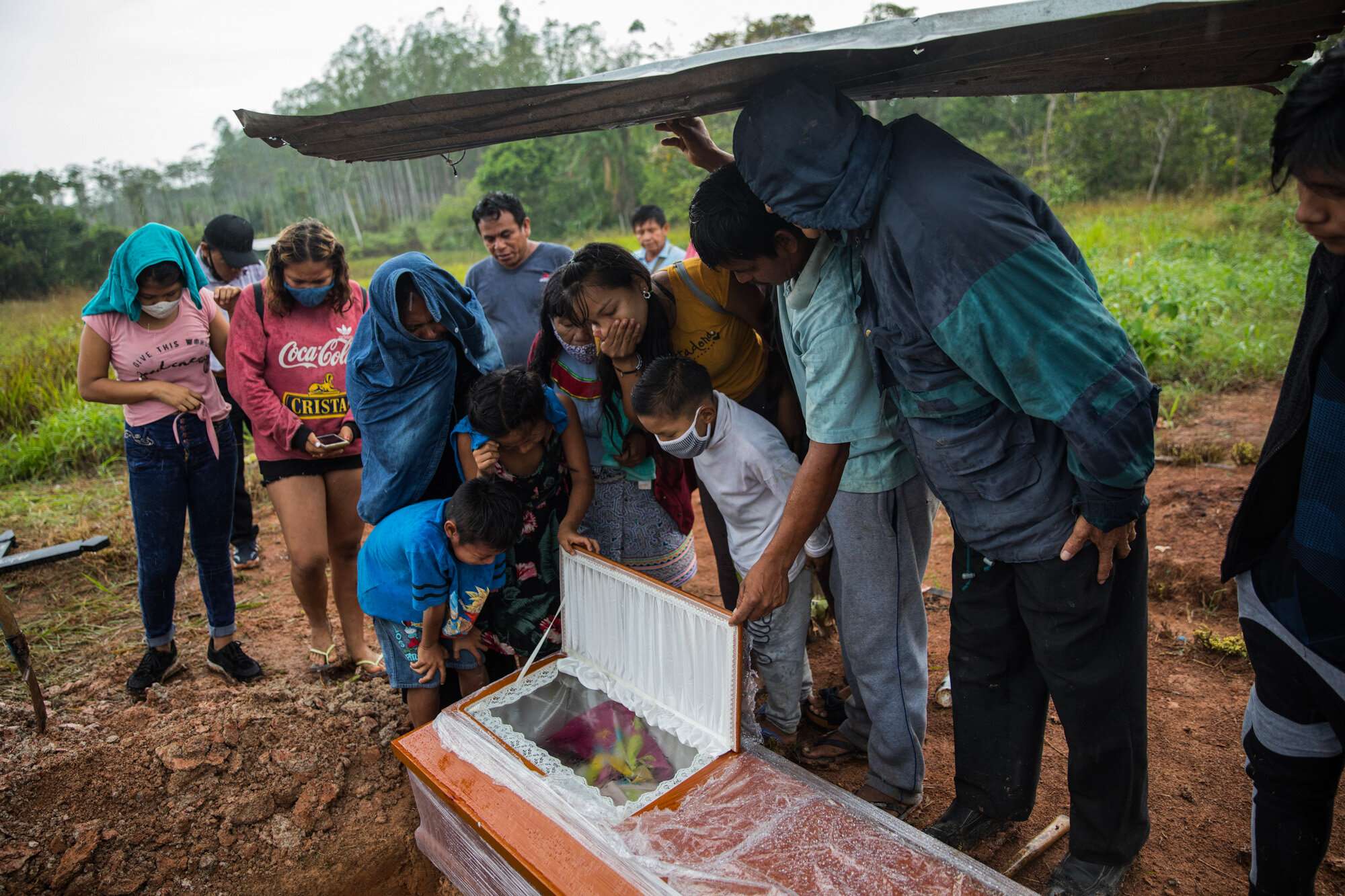 Family members peer into the coffin that contains the remains of Manuela Chavez, who died from symptoms related to the coronavirus at the age of 88, during a burial service in the Shipibo indigenous community of Pucallpa, in Peru's Ucayali region, on Aug. 31, 2020. (AP Photo/Rodrigo Abd)