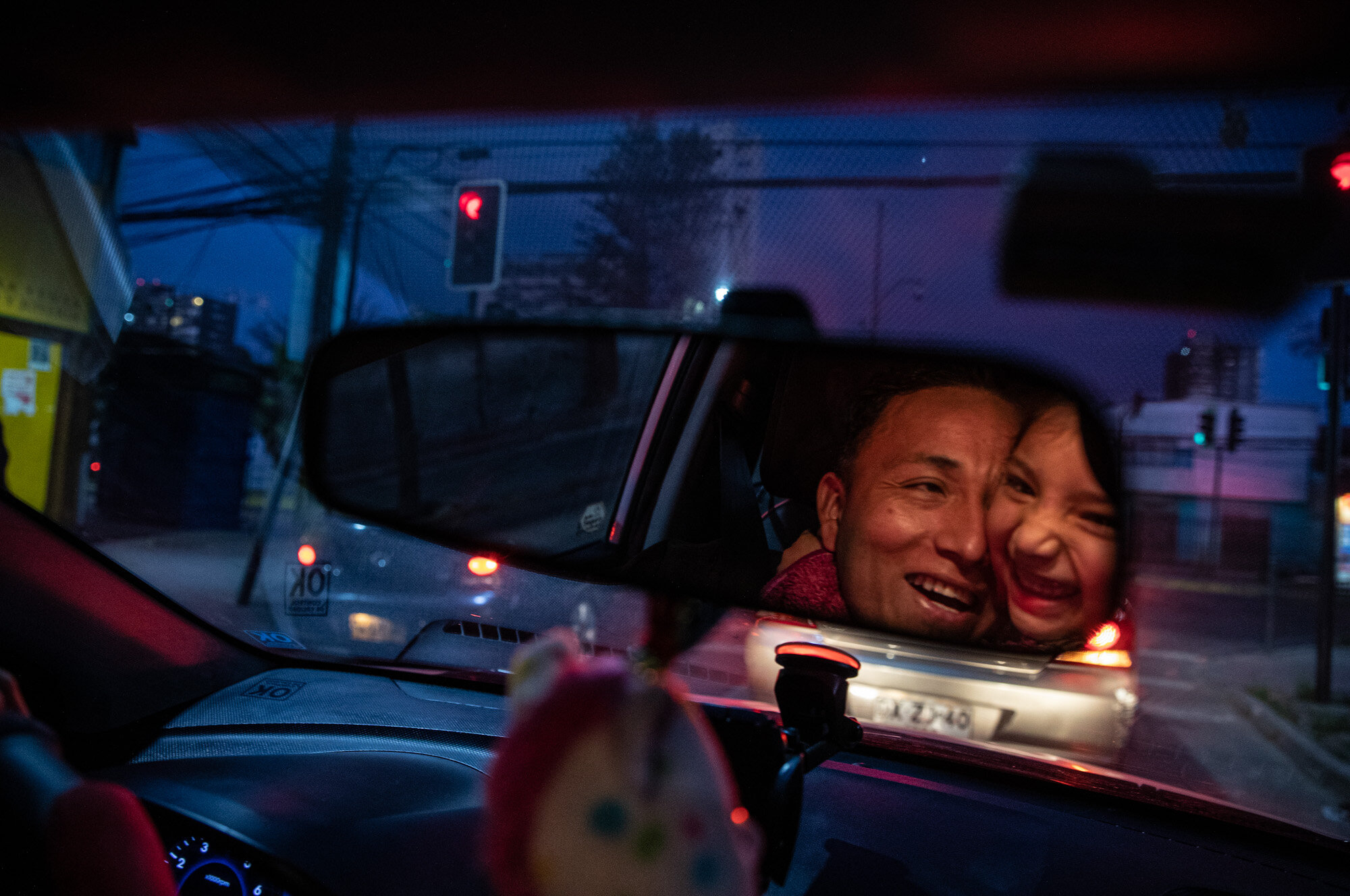 Reflected in the rearview mirror, Jose Collantes gets a hug from 5-year-old daughter Kehity while they're stopped at a red light, as Jose drives her home from a playdate in Santiago, Chile, on Sept. 6, 2020, three months after they lost his wife, her mother, to COVID-19. Their case highlights how COVID-19 deaths the world over are often the beginning of a new personal journey for those affected. (AP Photo/Esteban Felix)