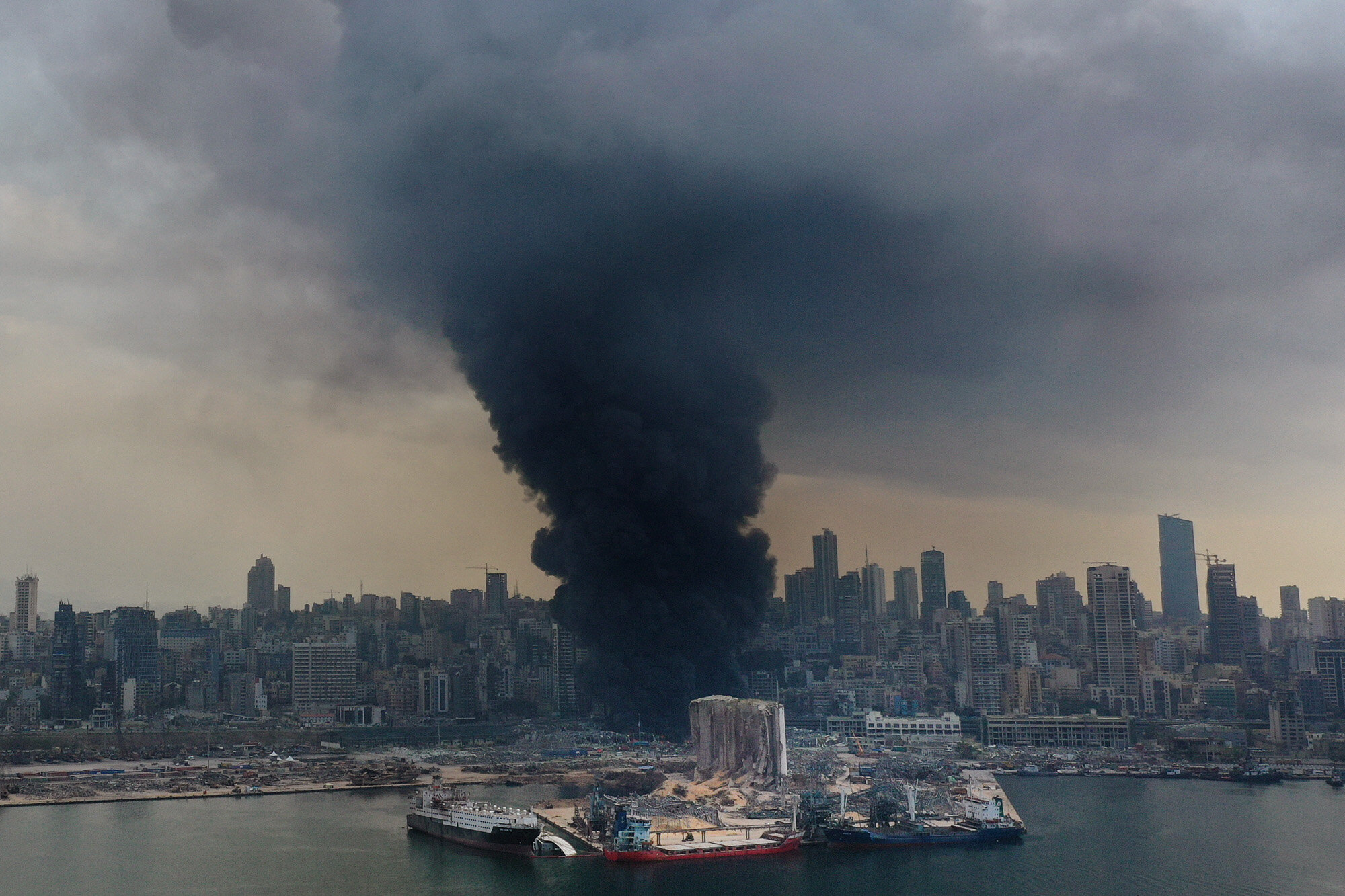 Black smoke rises from a warehouse fire at the Port of Beirut, Lebanon, on Sept. 10. 2020, triggering panic among residents traumatized by the massive explosion that killed and injured thousands of people the month before. (AP Photo/Hussein Malla)