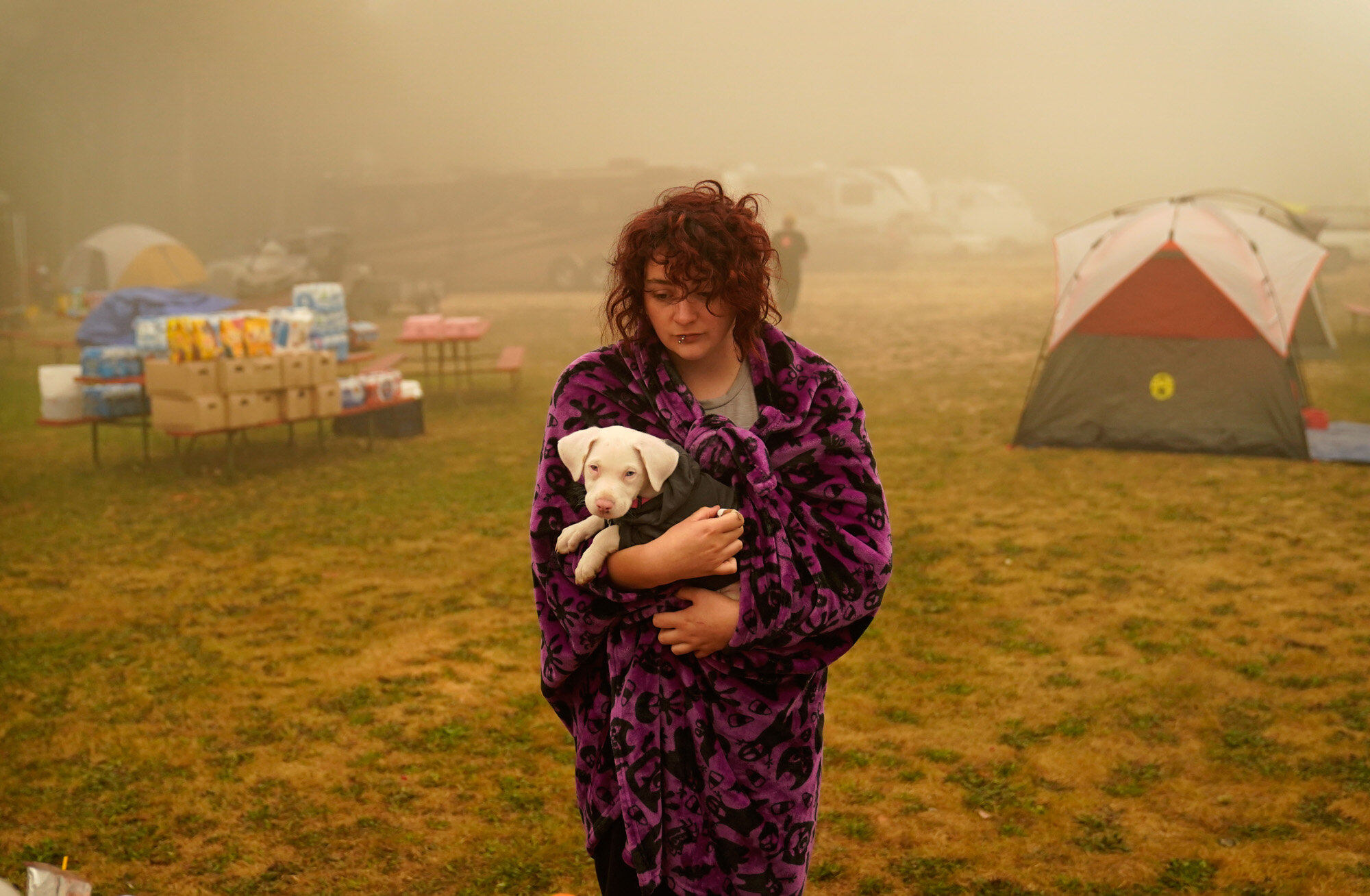 Shayanne Summers holds her dog Toph while wrapped in a blanket on Sept. 13, 2020, after staying several days in a tent at an evacuation center at the Milwaukie-Portland Elks Lodge in Oak Grove, Ore. Summers evacuated from near Molalla, Ore., which was threatened by the Riverside Fire. (AP Photo/John Locher)