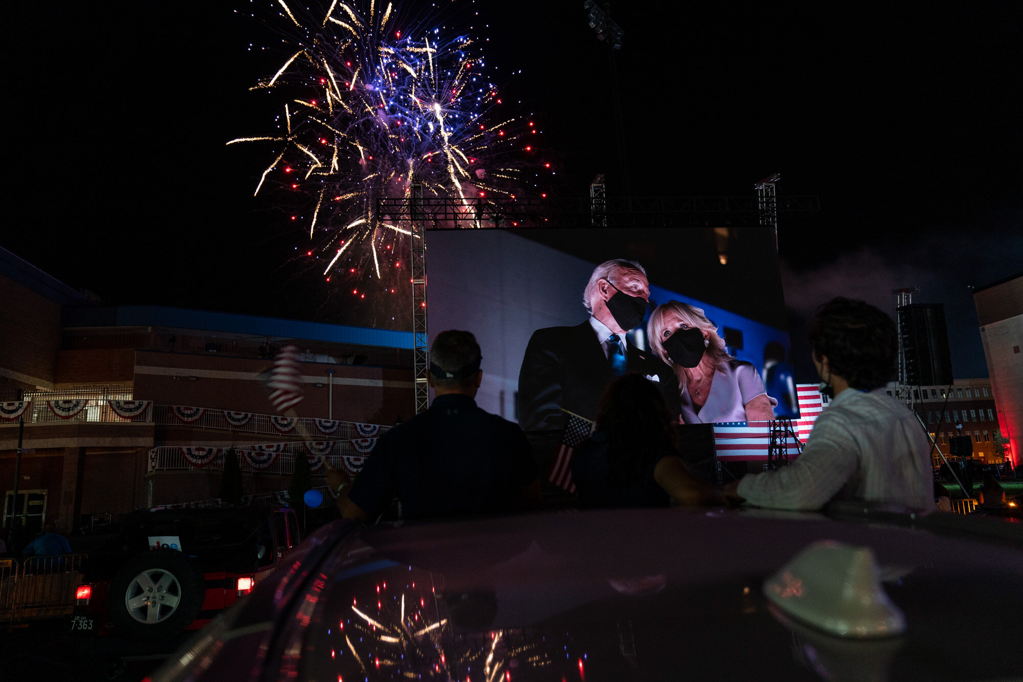 Supporters cheer from their cars as Democratic presidential candidate former Vice President Joe Biden and his wife Jill Biden appear on a huge monitor and fireworks light up the night sky on the fourth day of the Democratic National Convention in Wilmington, Del., on Aug. 20, 2020. (AP Photo/Carolyn Kaster)
